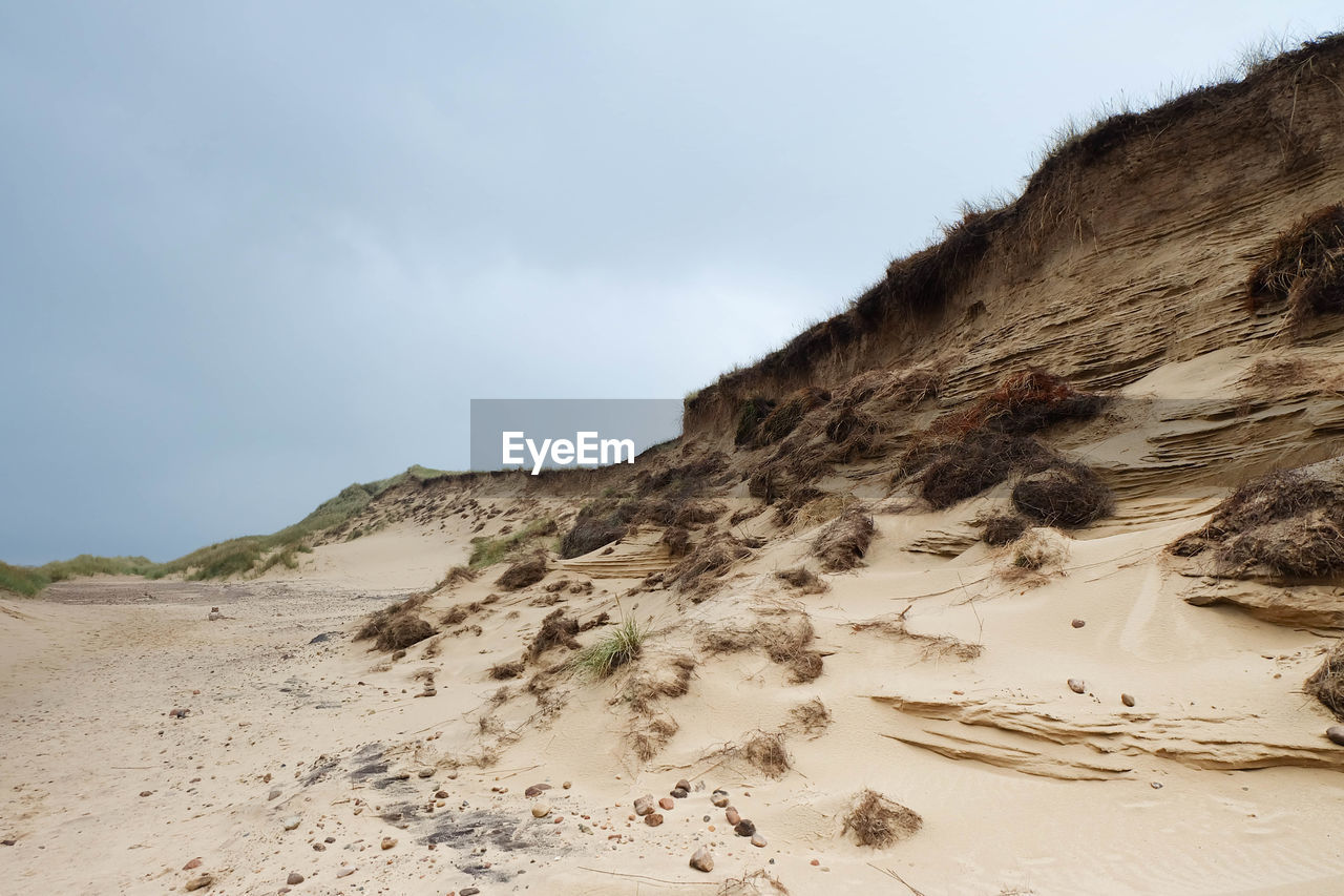 Scenic view of sandy beach against cloudy sky