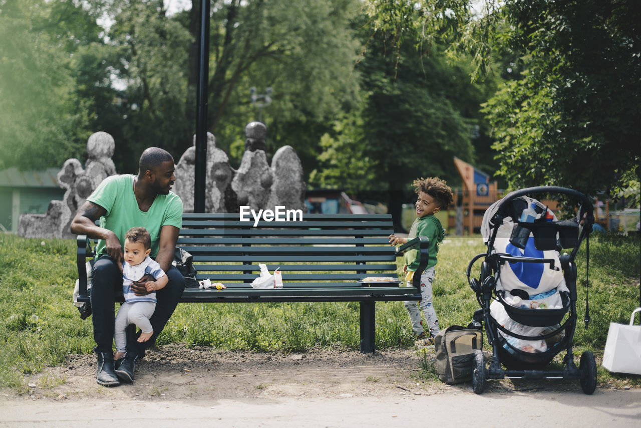 bench, group of people, real people, men, leisure activity, full length, sitting, plant, tree, males, day, boys, child, casual clothing, nature, lifestyles, childhood, park, seat, togetherness, outdoors, park bench, adolescence