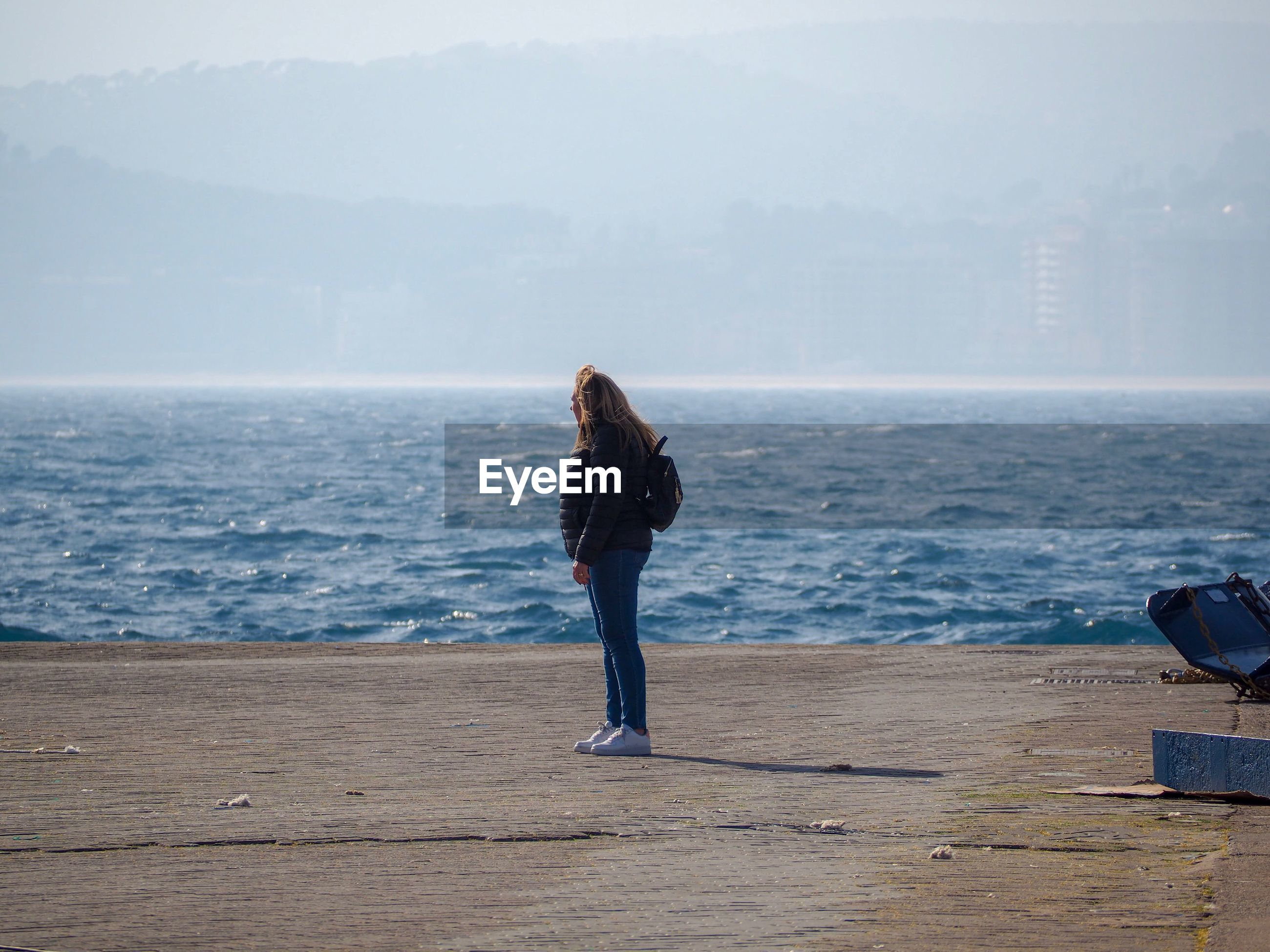 Woman looking away while standing against sea