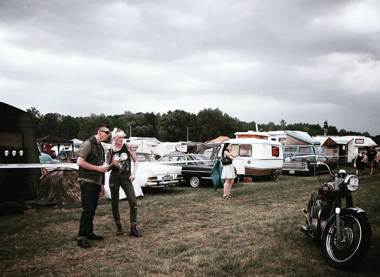 cloud - sky, sky, mode of transport, transportation, car, stationary, day, full length, outdoors, land vehicle, field, motor home, standing, real people, men, young adult, grass, storm cloud, building exterior, nature, young women, tree, one person, people