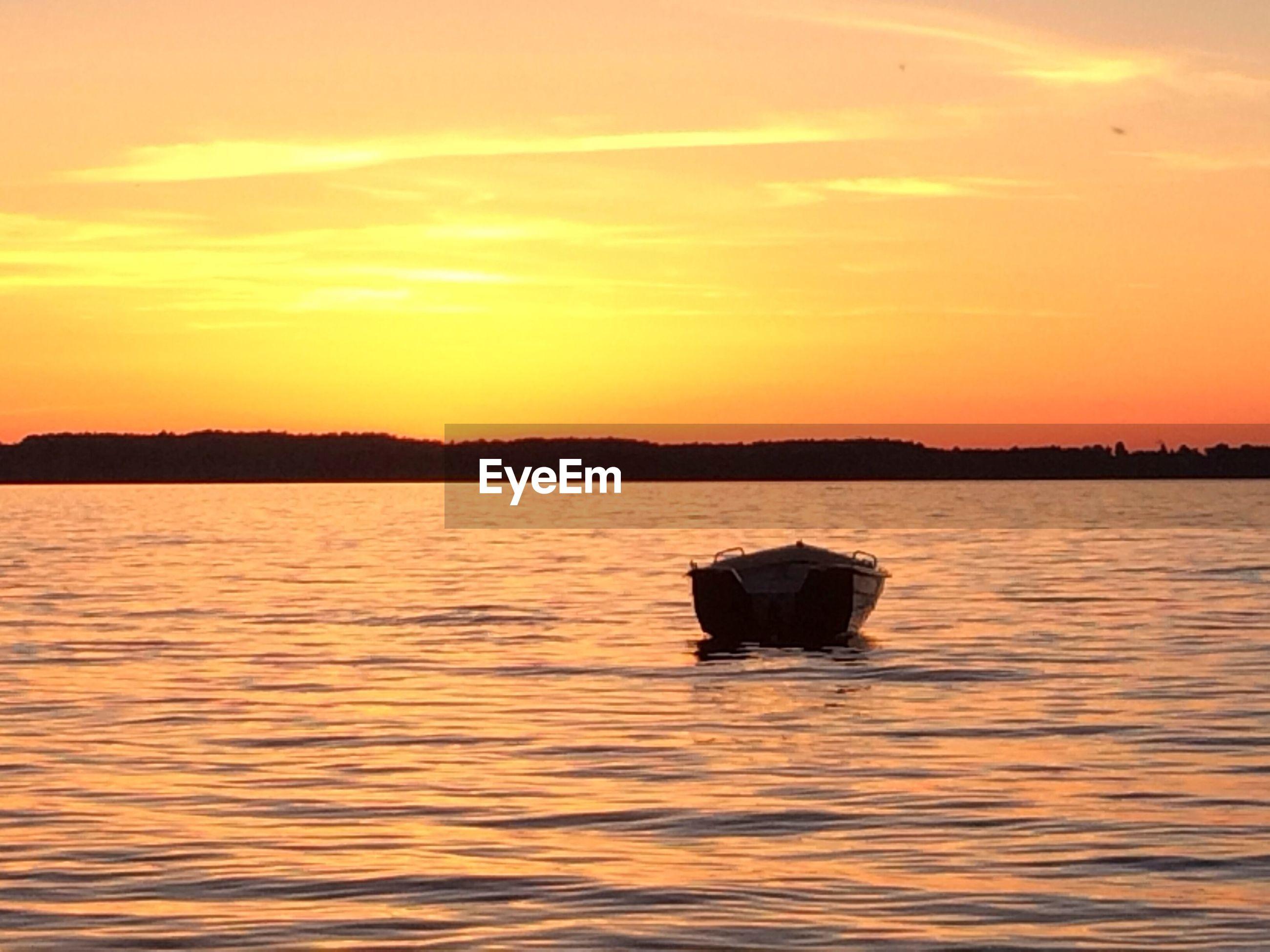Lone boat in calm sea against scenic sky