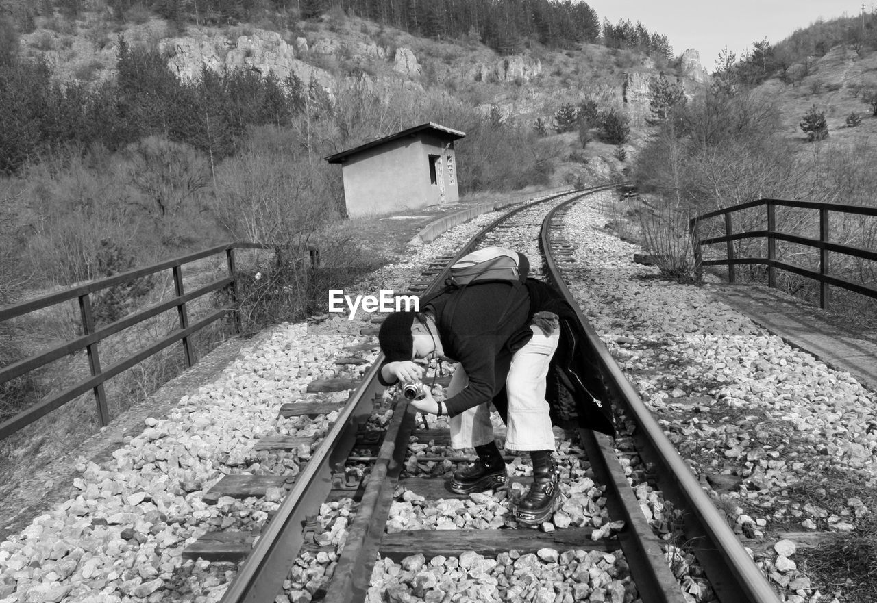 rail transportation, railroad track, track, architecture, transportation, built structure, one person, railing, day, nature, mode of transportation, sitting, plant, tree, public transportation, outdoors, men, adult, full length, social issues