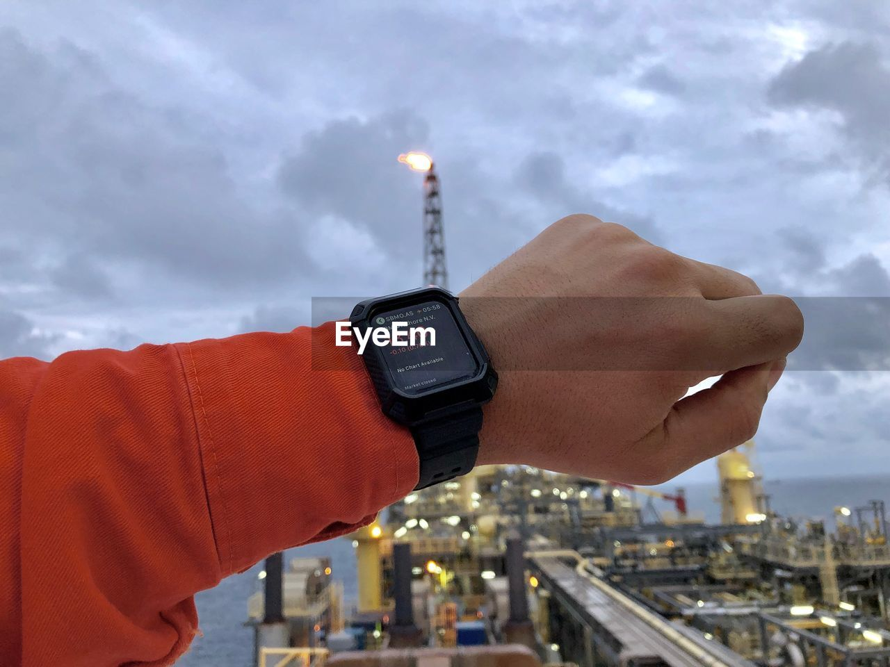 human hand, cloud - sky, hand, technology, building exterior, human body part, holding, communication, one person, architecture, focus on foreground, built structure, sky, city, wireless technology, time, connection, real people, body part, outdoors, cityscape, finger, human limb