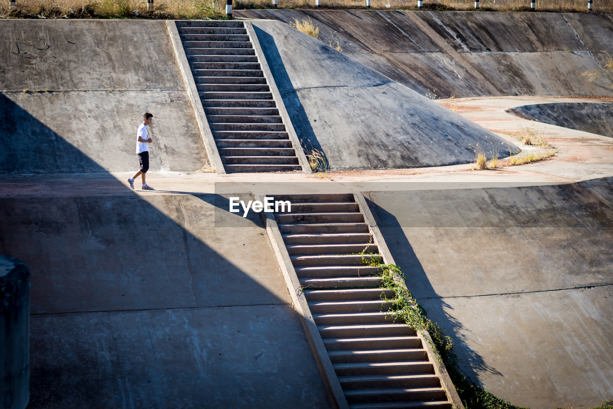Side view of teenage boy walking on dam