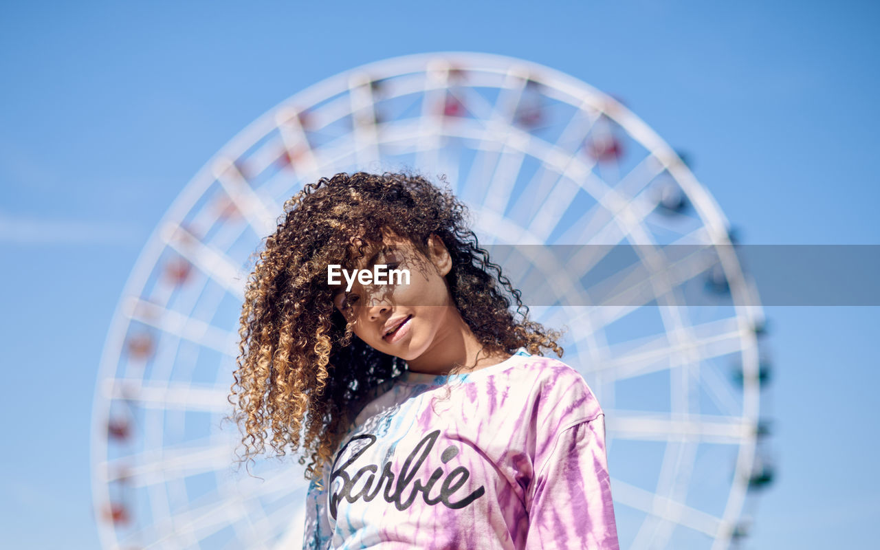 Portrait Of Beautiful Young Woman With Curly Hair Against Ferris Wheel