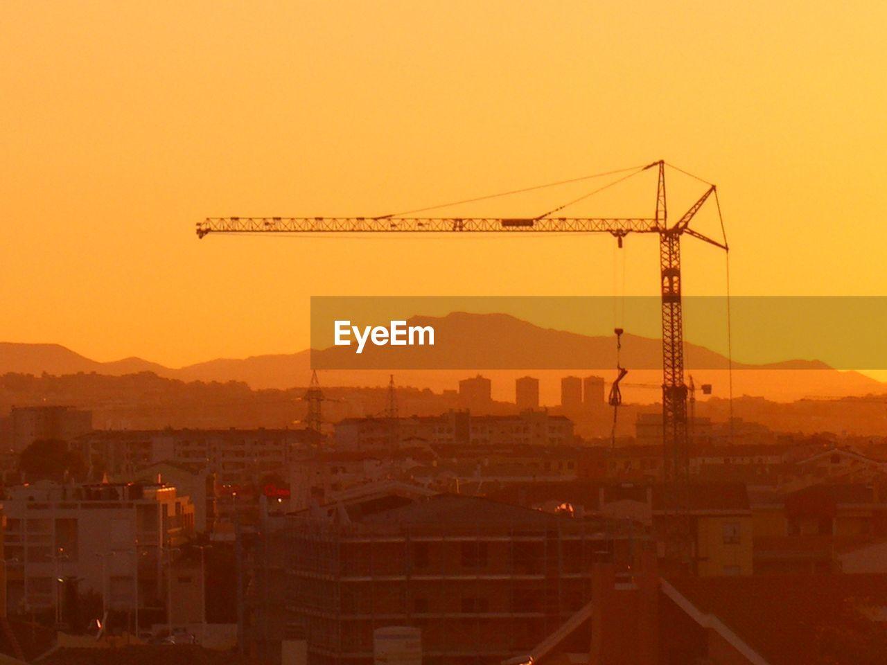 Silhouette Crane And Buildings Against Orange Sky