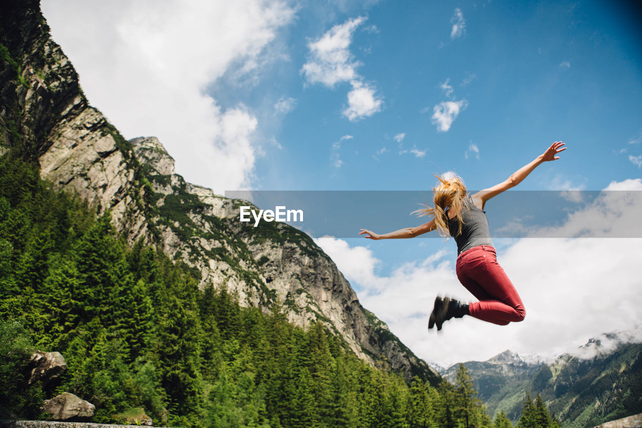 Young Woman Jumping Against Mountain And Sky