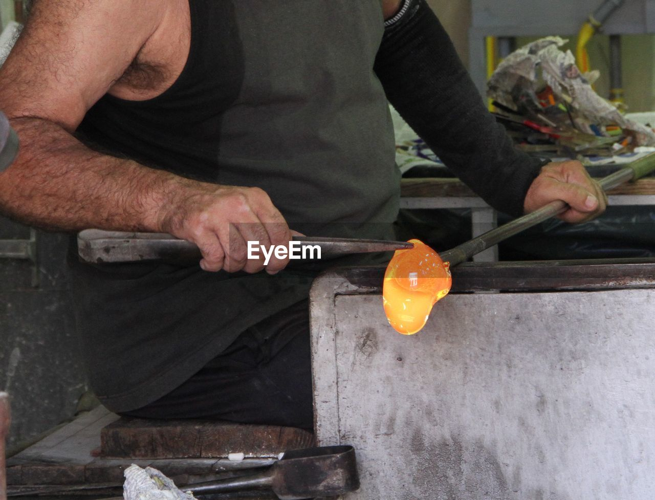 Manual Worker Holding Glass Blower In Glass Factory