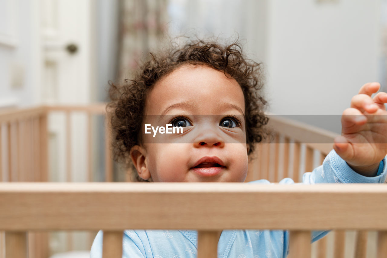 child, childhood, portrait, innocence, real people, baby, front view, cute, people, lifestyles, young, indoors, focus on foreground, looking at camera, females, curly hair, crib, headshot