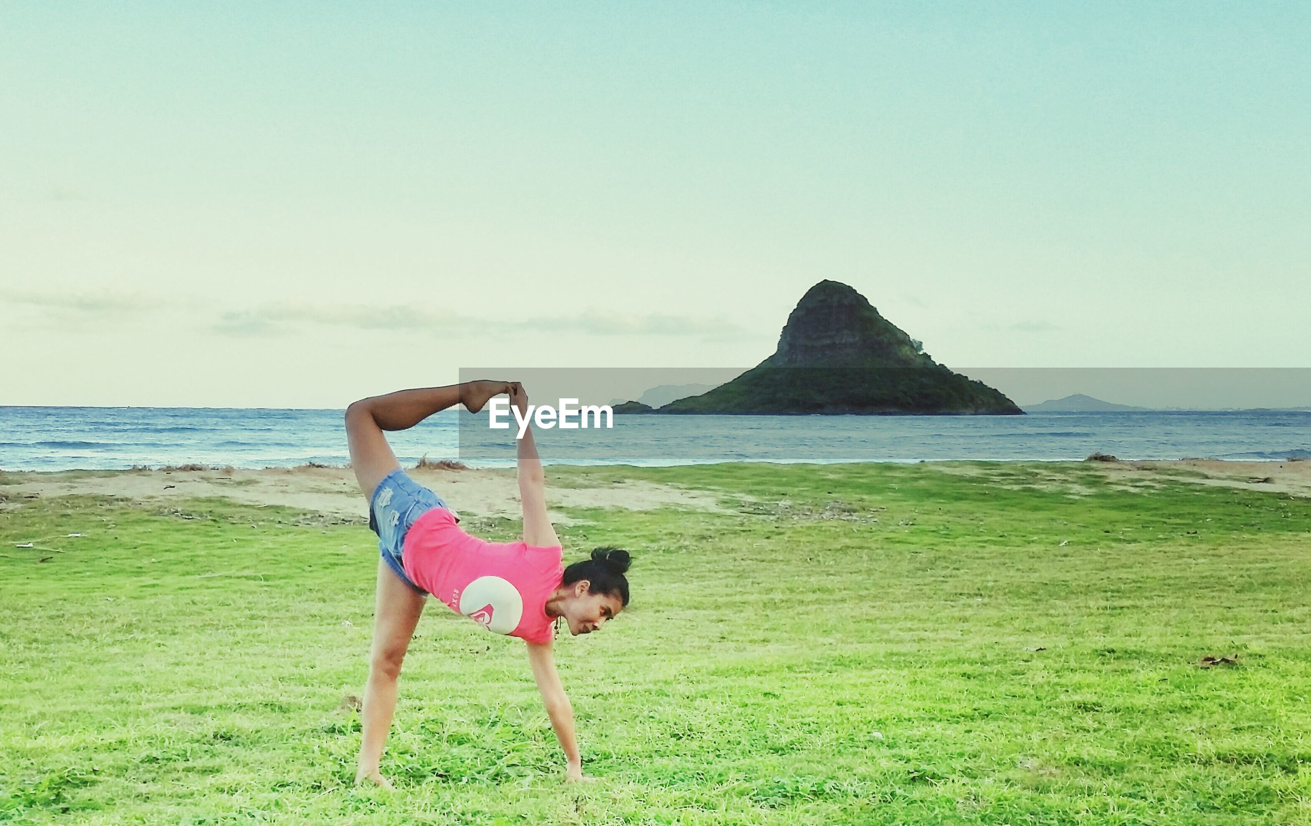 Woman doing yoga on lawn against sea