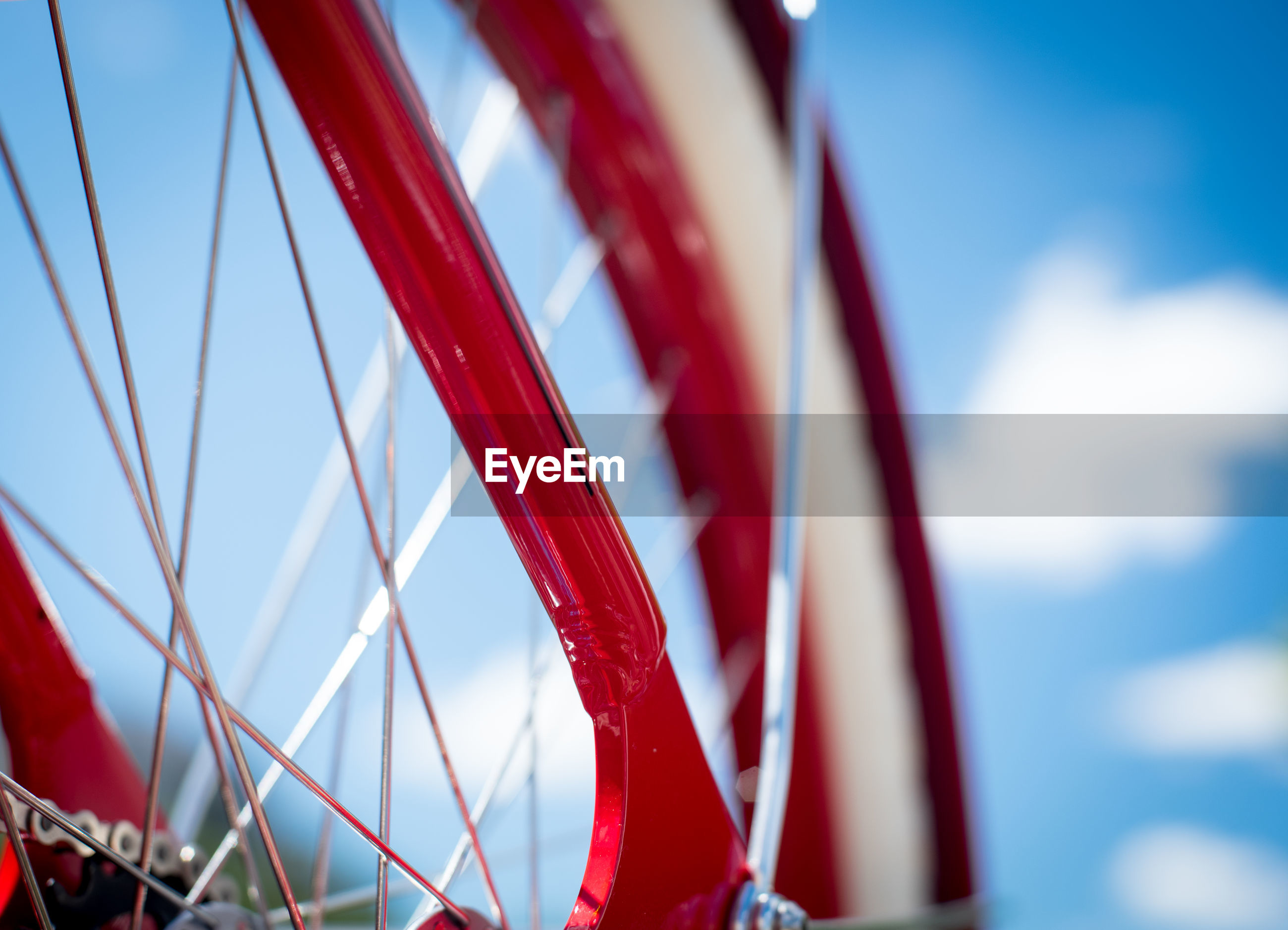 Low angle view of red bicycle wheel against sky