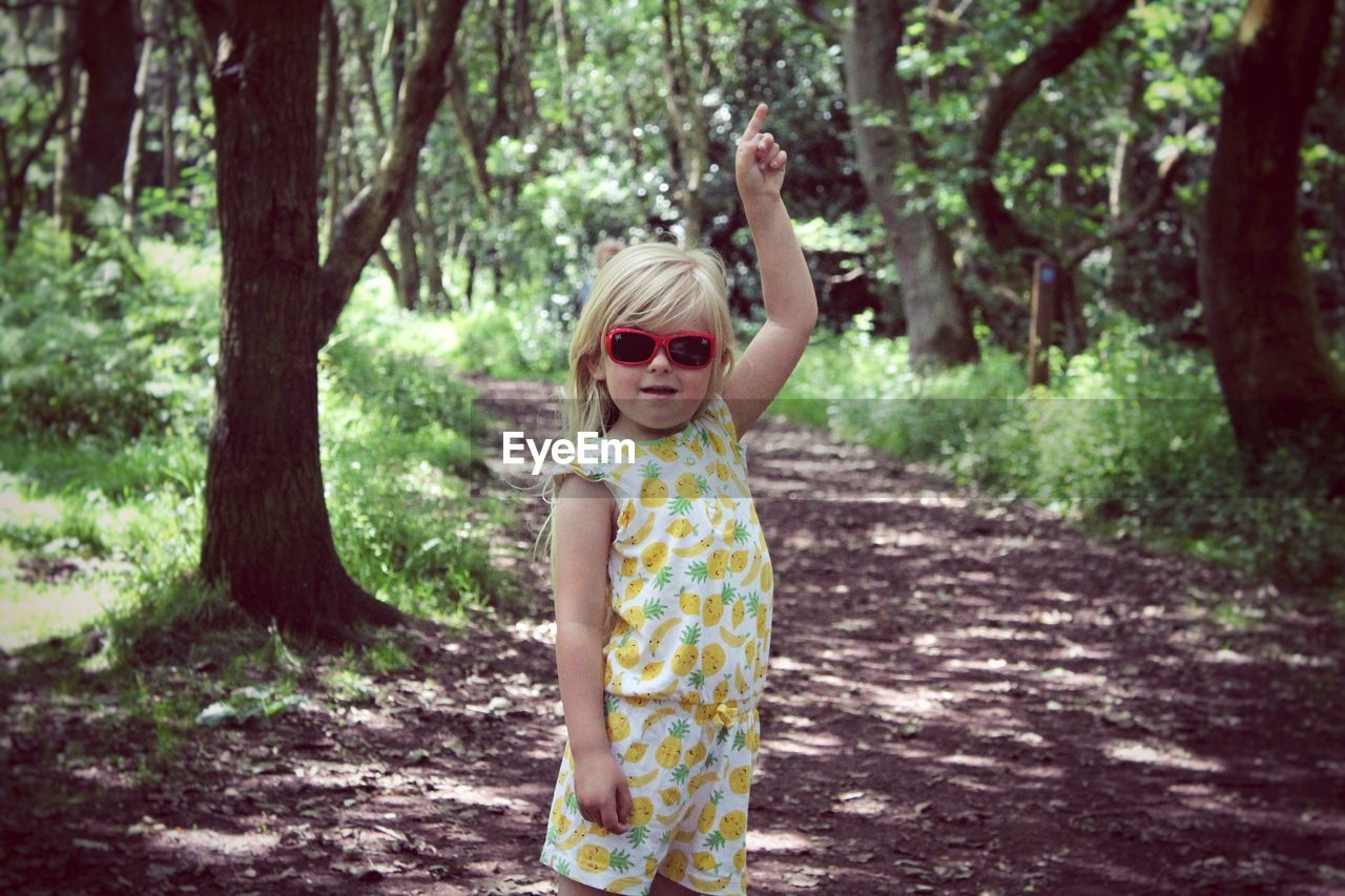 Portrait Of Girl Wearing Sunglasses While Pointing In Forest