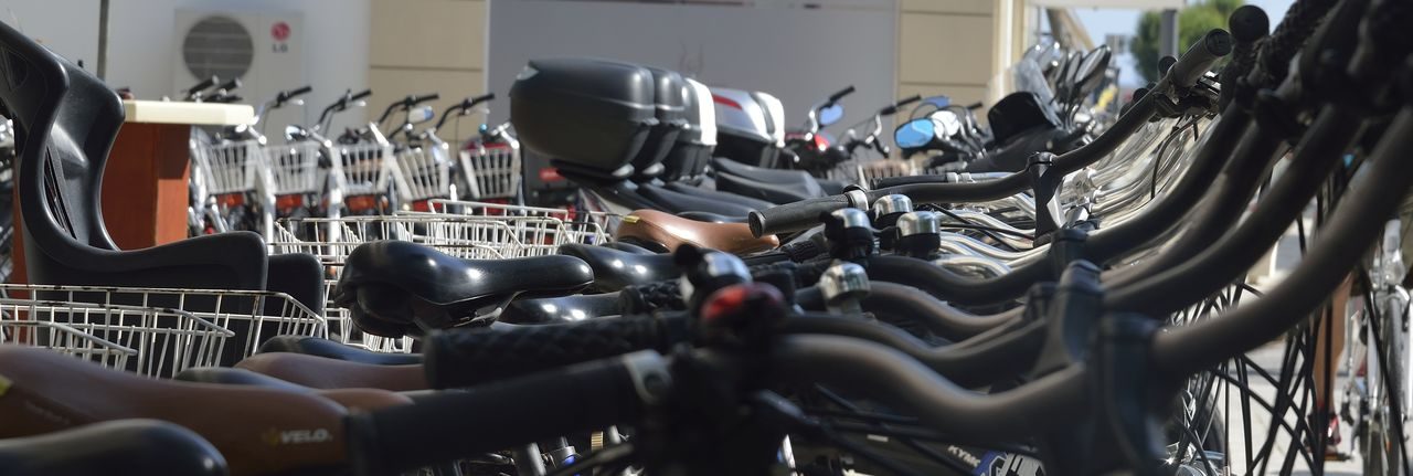in a row, bicycle, selective focus, rack, no people, large group of objects, indoors, metal, close-up, stationary, land vehicle, black color, abundance, business, absence, sport, mode of transportation, transportation, handlebar, day