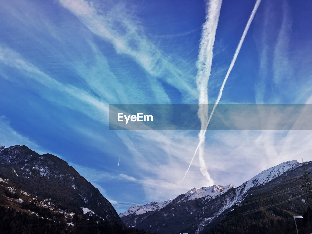 Low angle view of vapor trails in sky over rocky mountains