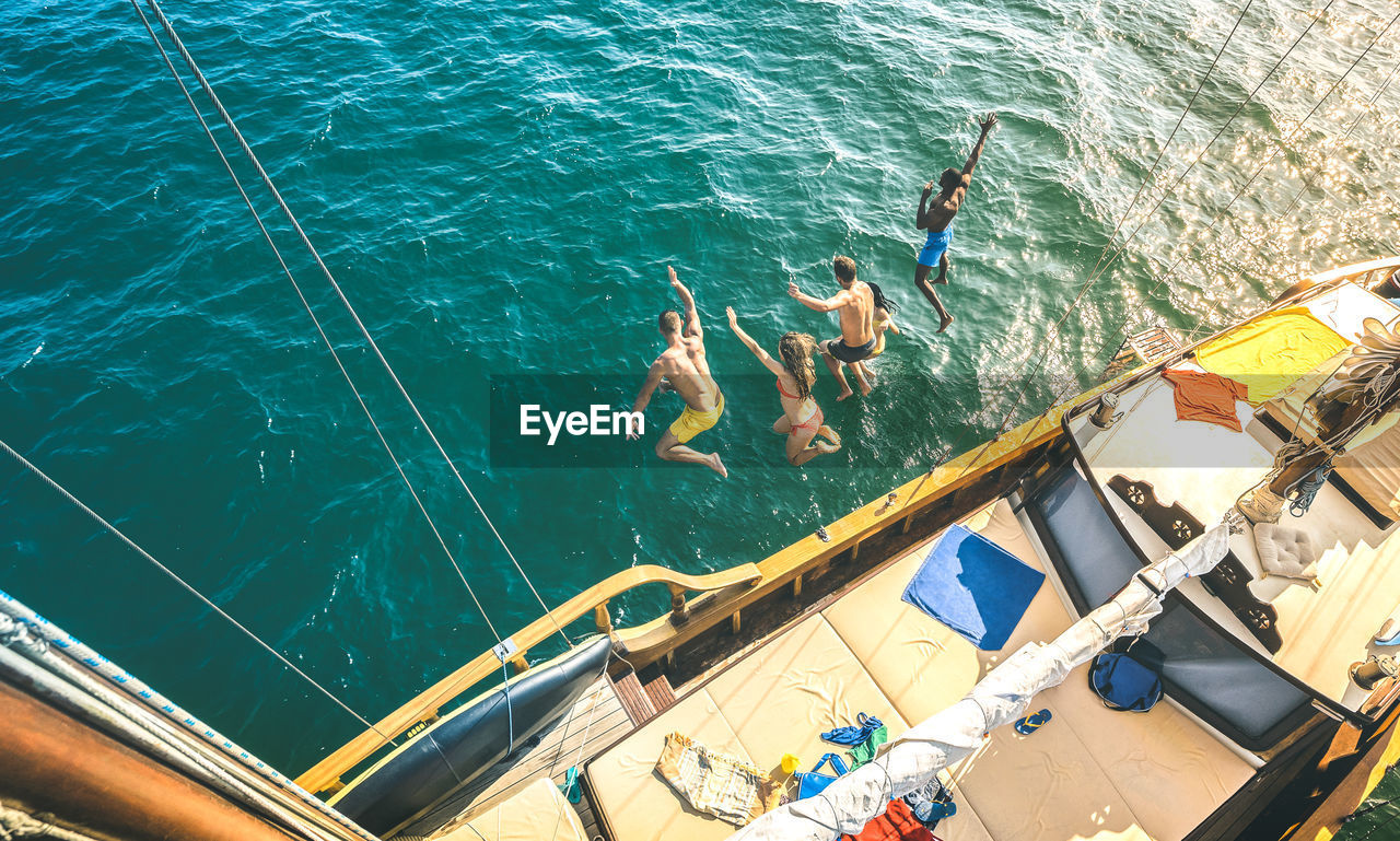 water, sea, high angle view, nature, real people, swimming, day, swimwear, group of people, men, lifestyles, nautical vessel, people, leisure activity, clothing, outdoors, transportation, jumping, sunlight, turquoise colored