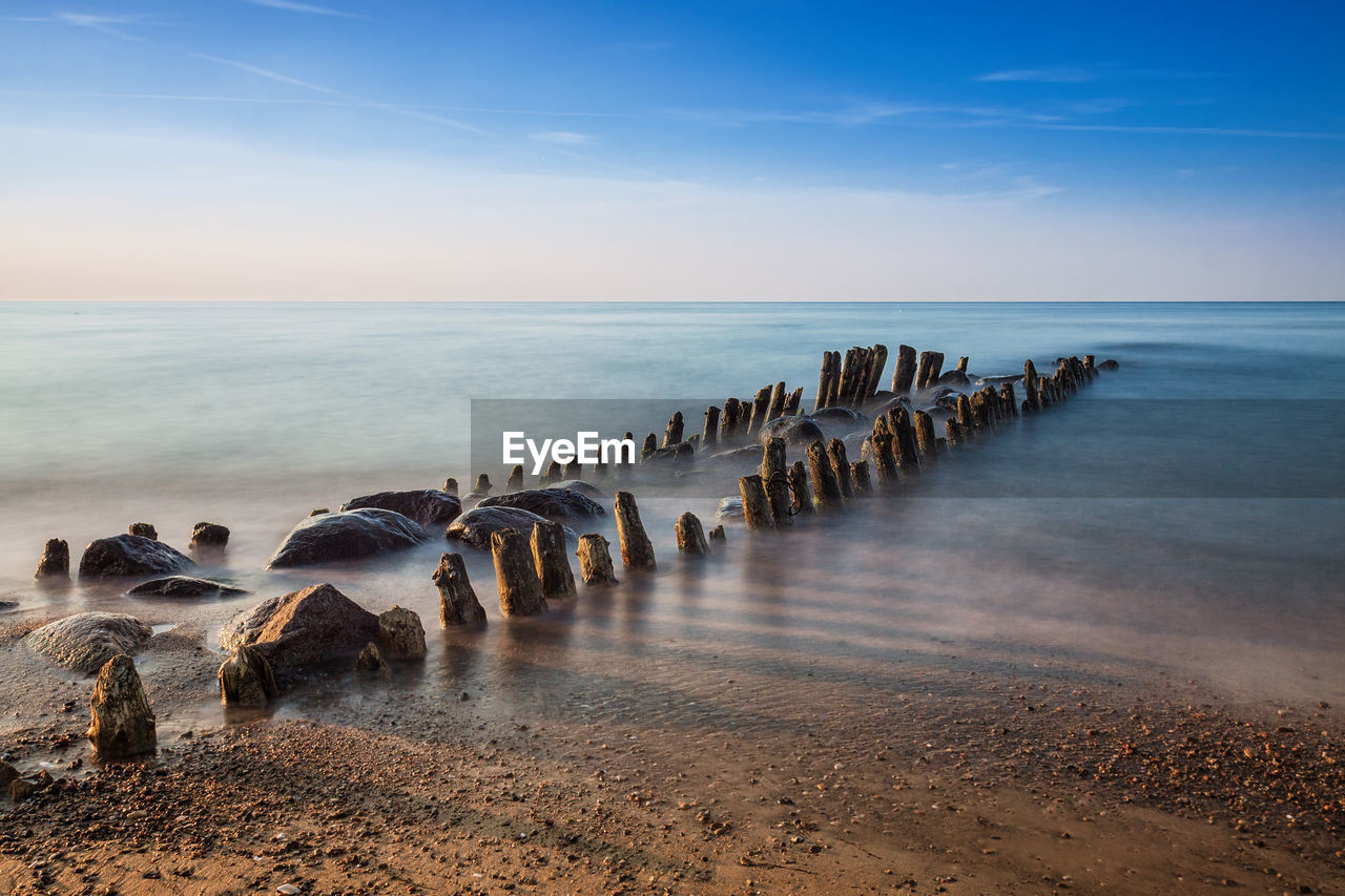 sea, water, sky, horizon over water, horizon, scenics - nature, beauty in nature, beach, land, tranquil scene, tranquility, nature, idyllic, no people, non-urban scene, day, motion, outdoors, cloud - sky, wooden post, groyne