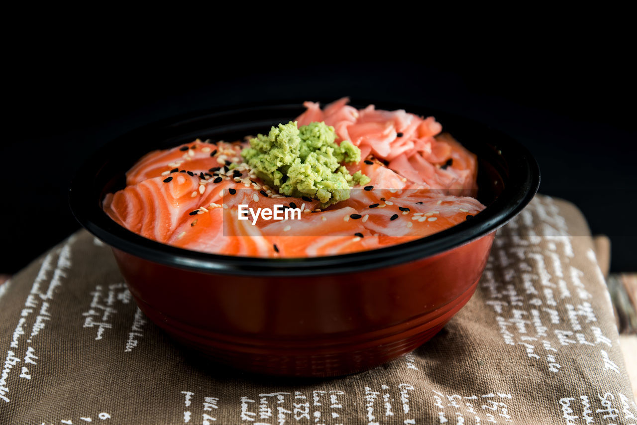 food, food and drink, freshness, healthy eating, indoors, ready-to-eat, close-up, bowl, asian food, still life, japanese food, wellbeing, no people, table, seafood, serving size, salmon - seafood, focus on foreground, black background, studio shot, sashimi, garnish, temptation