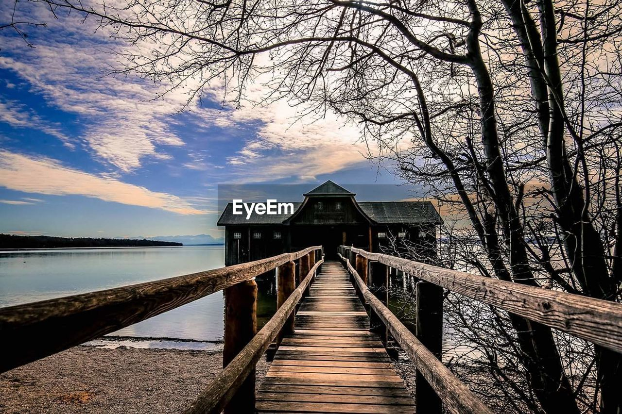 built structure, pier, water, wood - material, lake, bare tree, sky, nature, outdoors, tree, tranquility, architecture, tranquil scene, no people, jetty, cloud - sky, beauty in nature, scenics, day, covered bridge, branch