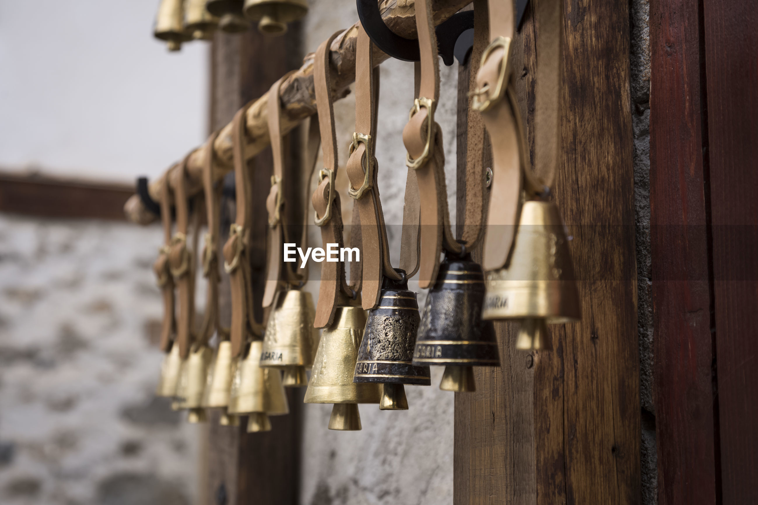 Close-up of bells hanging on wood with leather belt