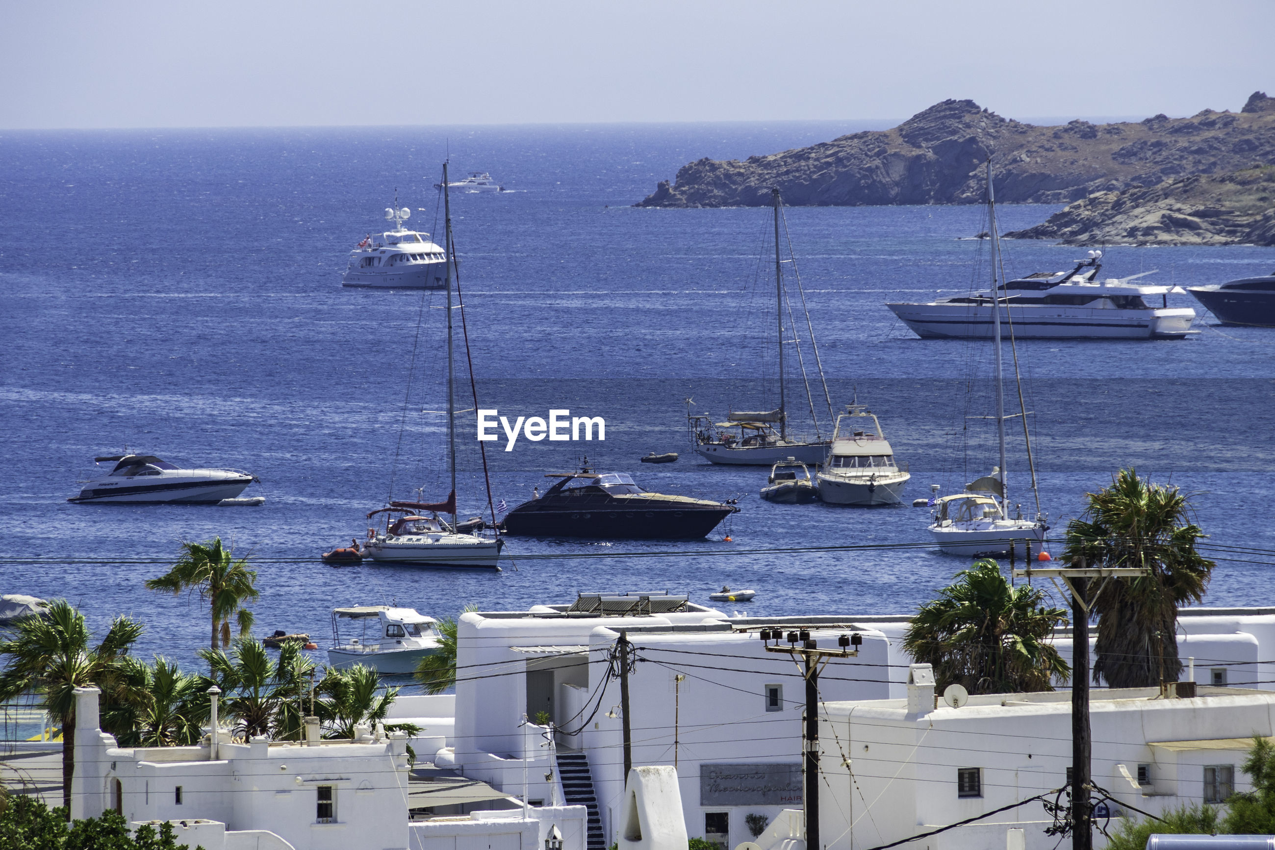 Sailboats, speedboats and yachts on sea in ornos bay mykonos against sky