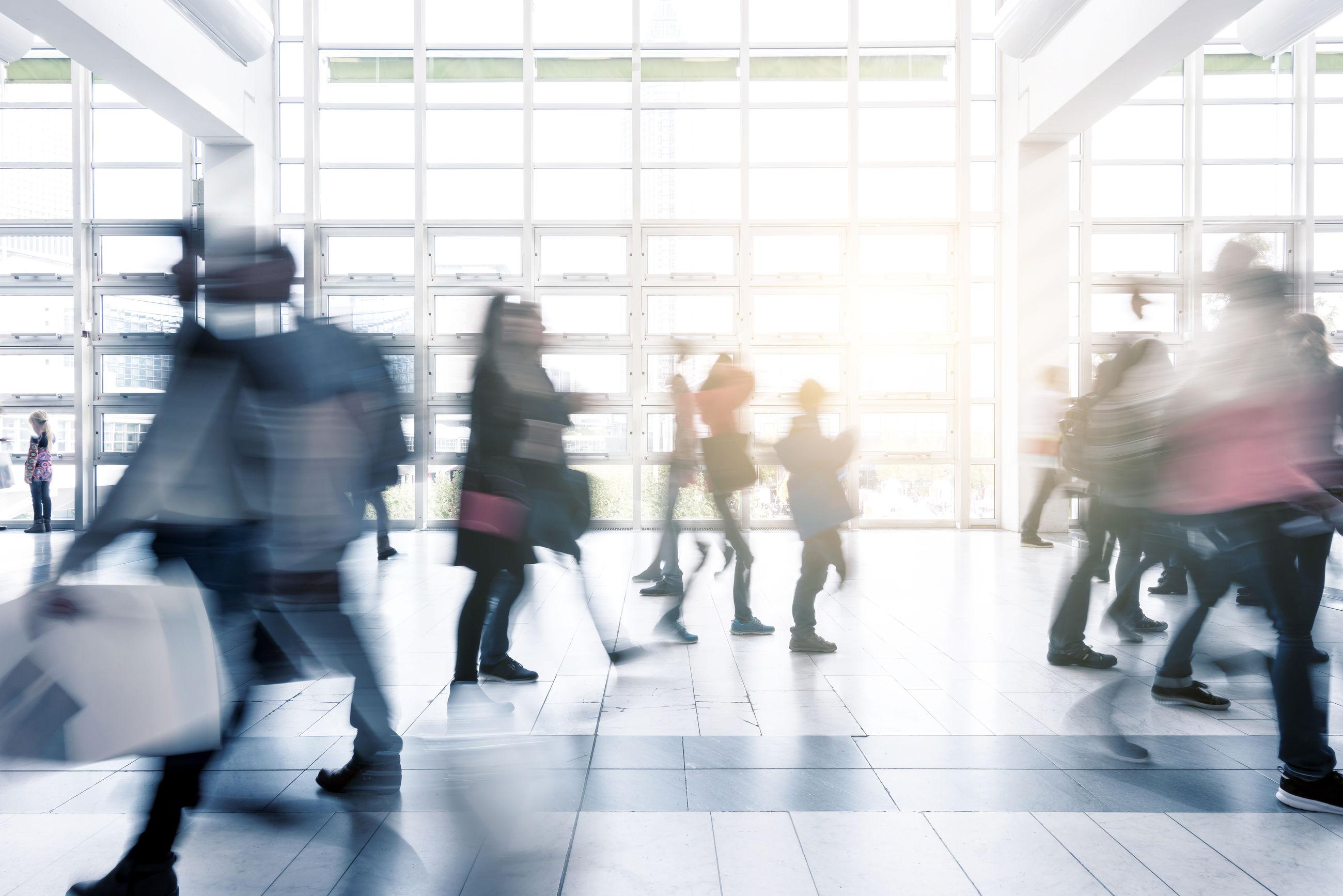 Blurred motion of people walking in modern office building