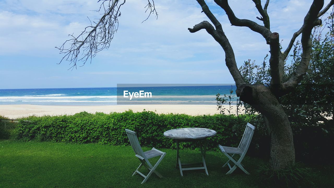 Empty Chairs And Table By Tree Against Beach