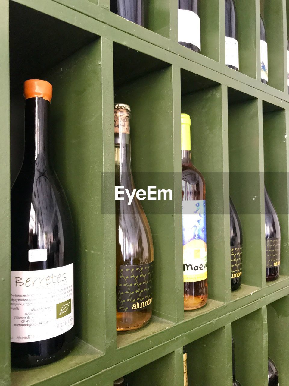 bottle, container, no people, green color, indoors, text, glass - material, food and drink, drink, alcohol, communication, wine bottle, shelf, label, refreshment, choice, still life, transparent, variation, close-up