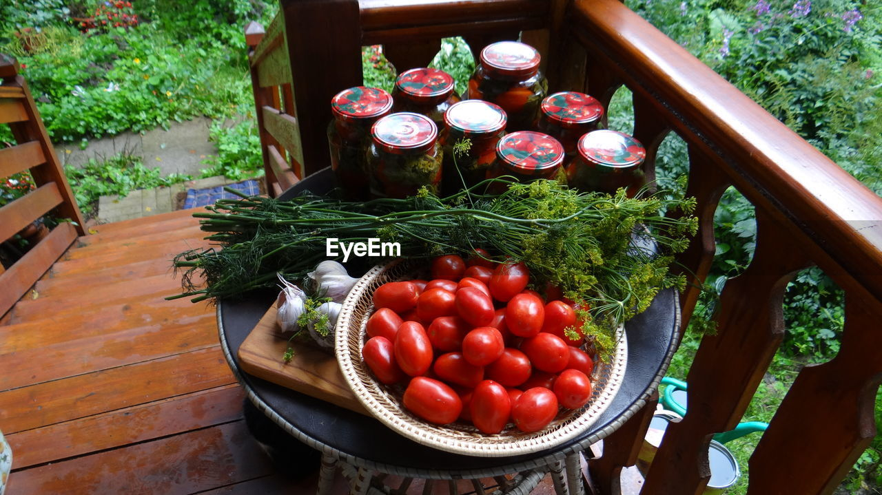 High Angle View Of Tomatoes In Bowl By Jars And Herbs On Table