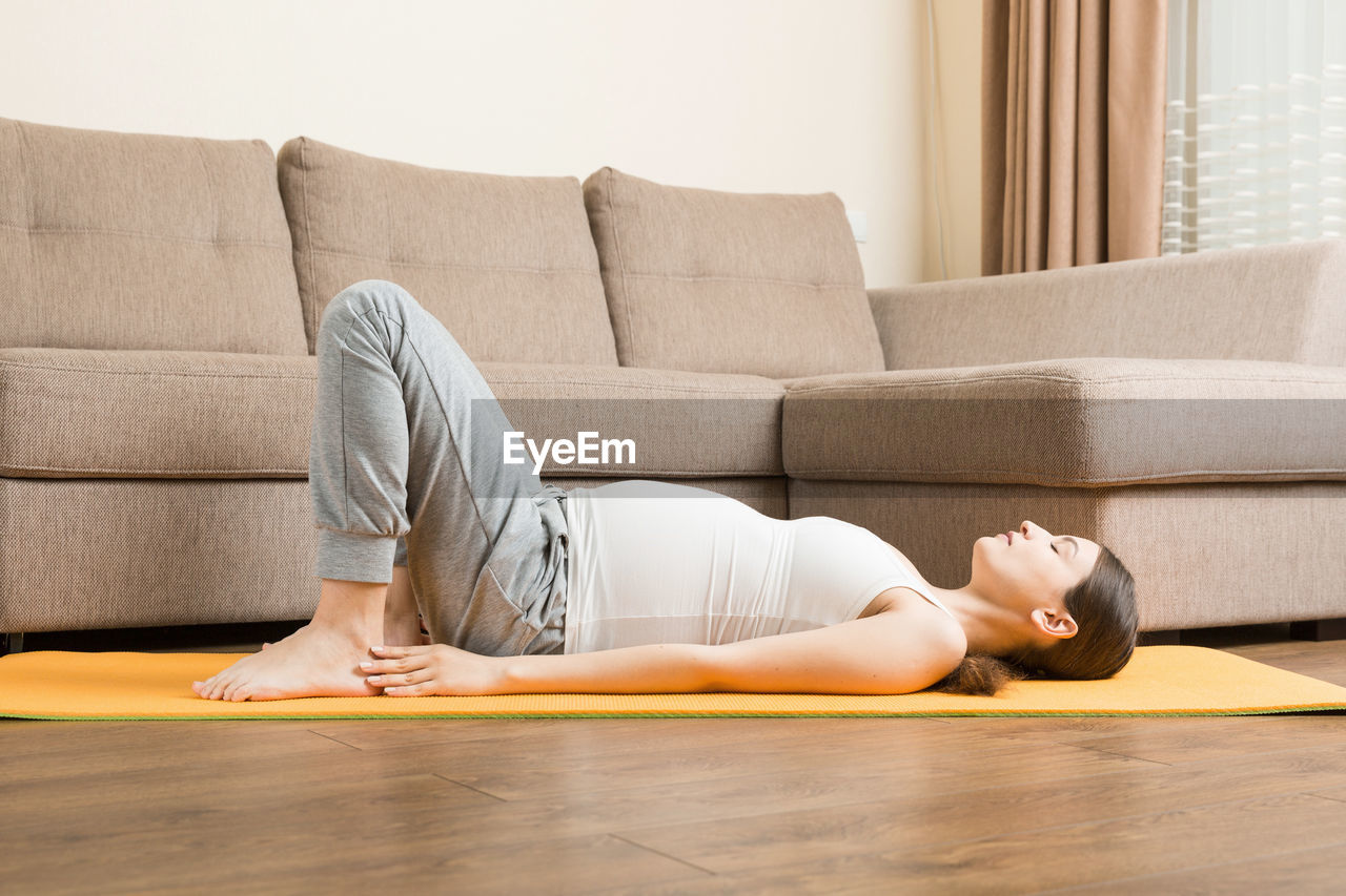 MIDSECTION OF MAN RELAXING ON SOFA