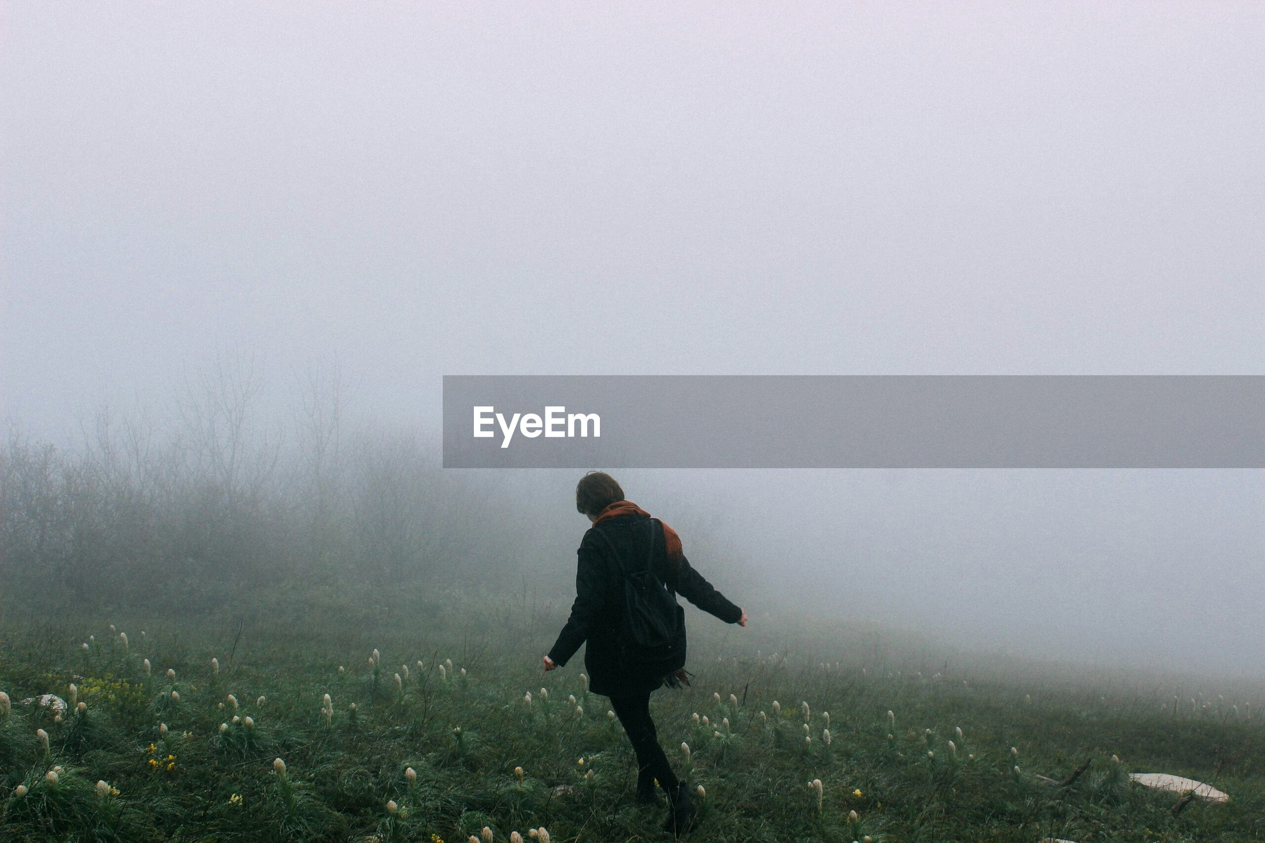 Woman walking in misty landscape at dawn