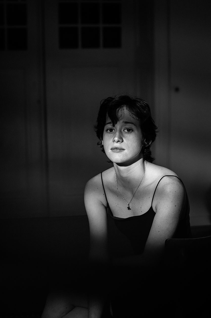 Portrait of thoughtful young woman sitting in darkroom