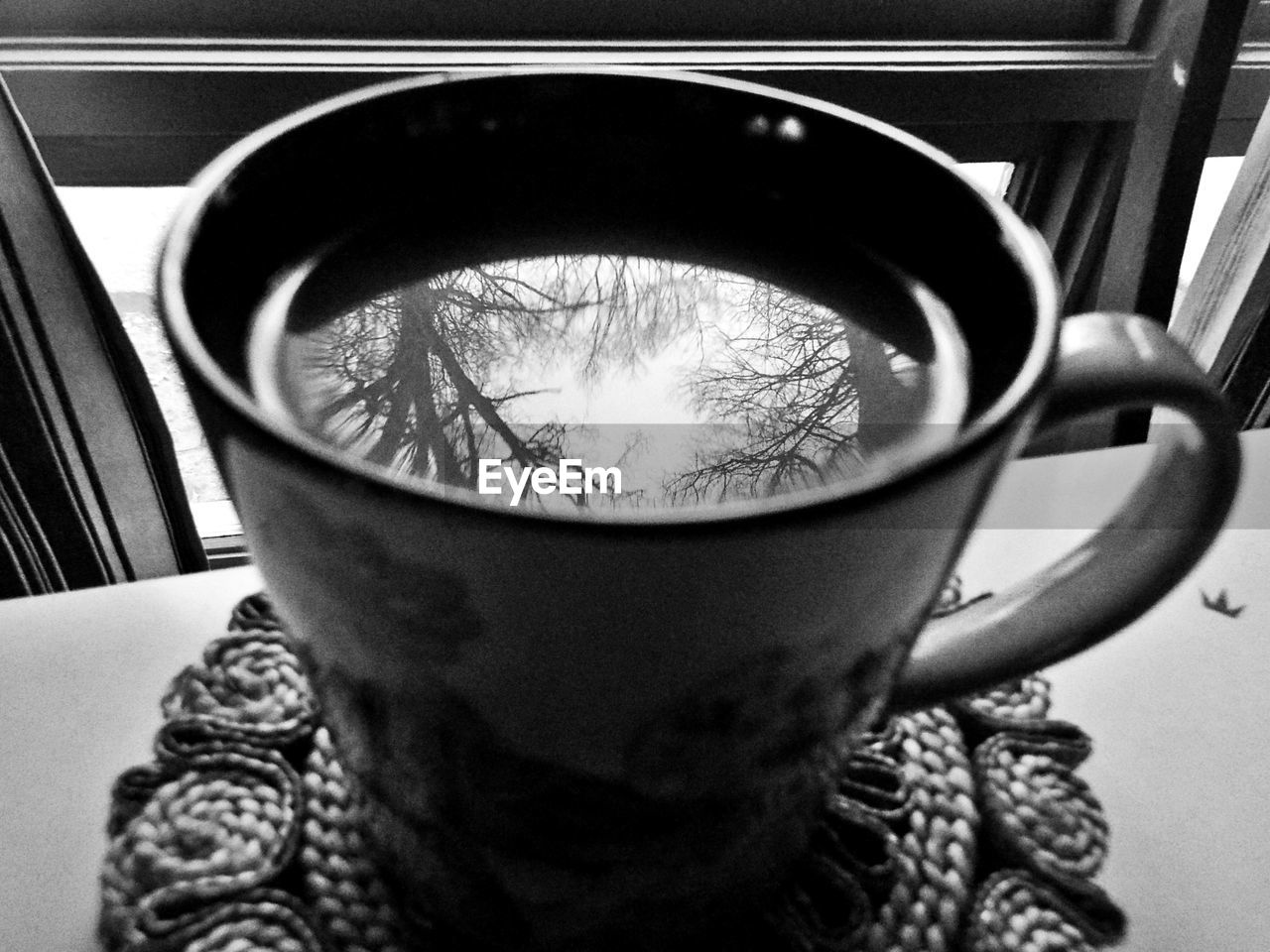 Reflection Of Bare Trees In Coffee On Table At Home