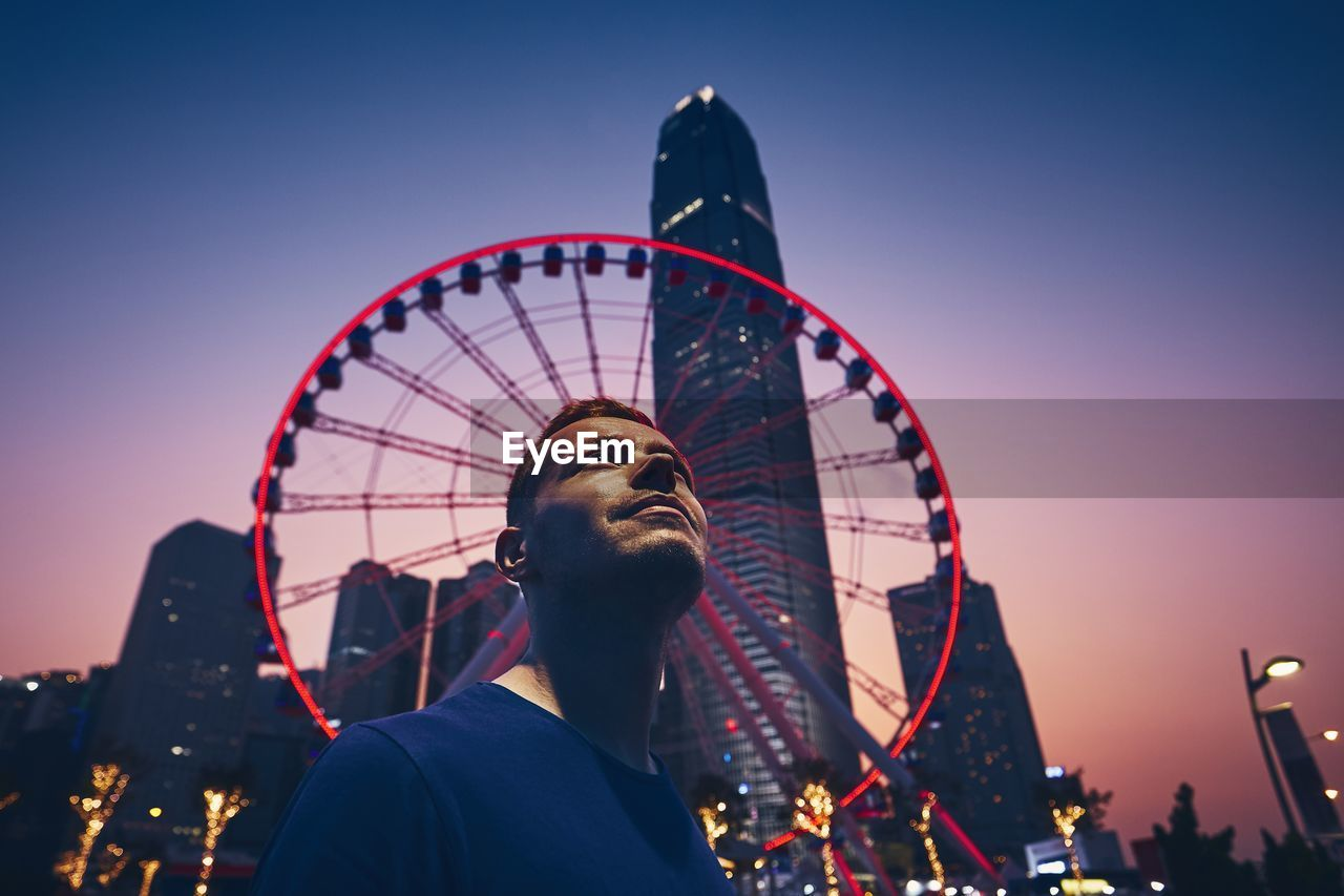 Low angle view of man against ferris wheel at dusk