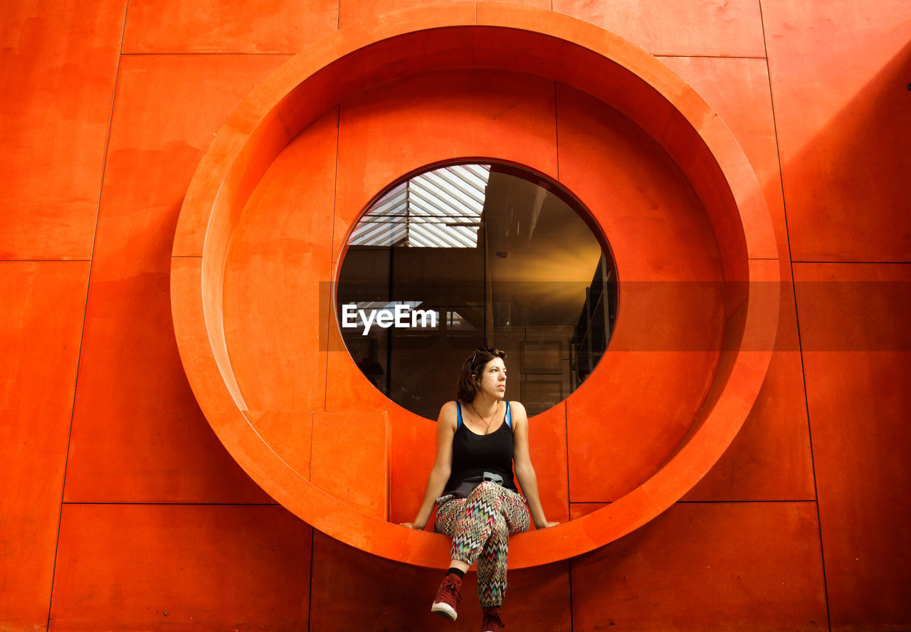 Full Length Of Woman Sitting On Window Of Orange Building