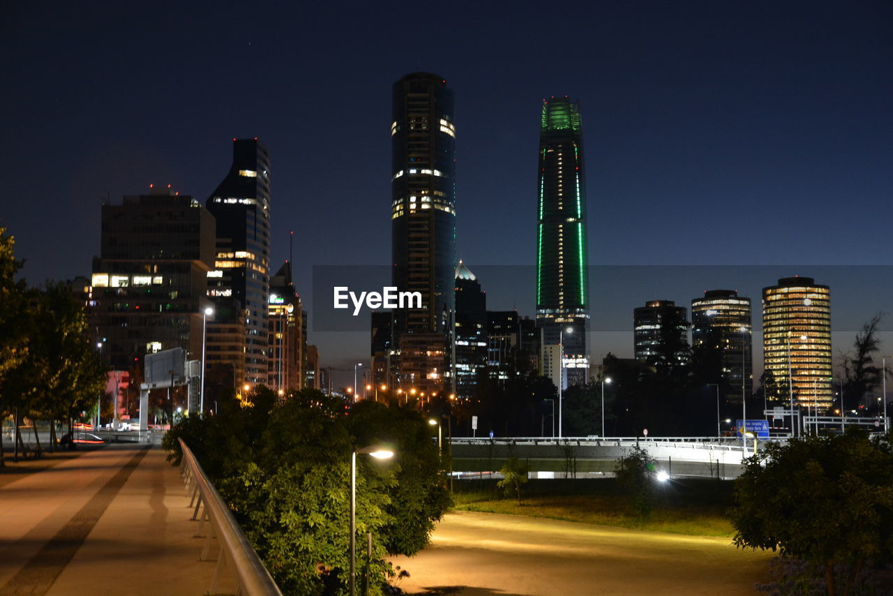 illuminated, night, architecture, built structure, building exterior, road, transportation, street light, city, sky, skyscraper, modern, clear sky, outdoors, no people, tall, tree