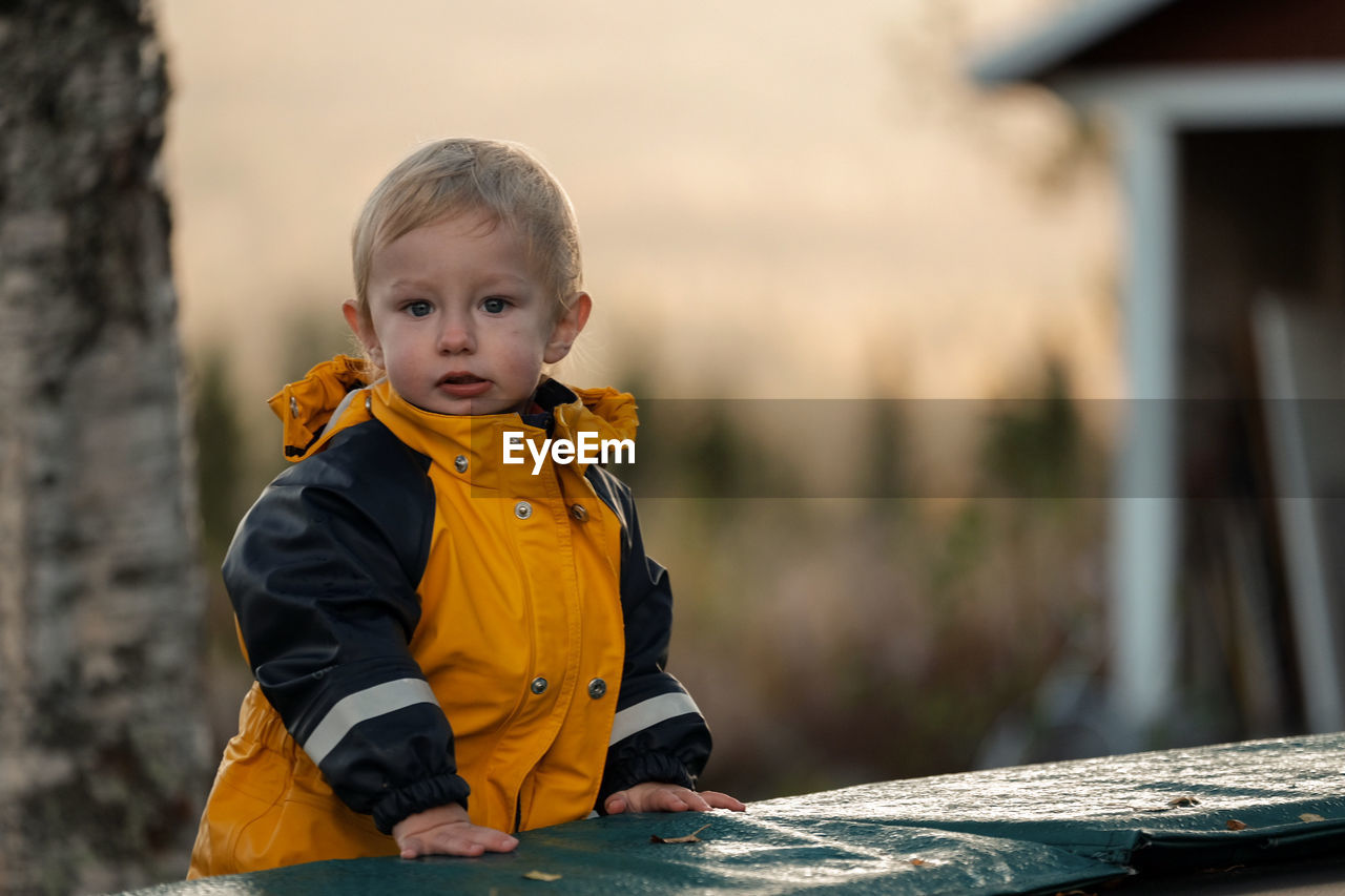 Portrait Of Cute Baby Boy Wearing Warm Clothing While Standing Outdoors