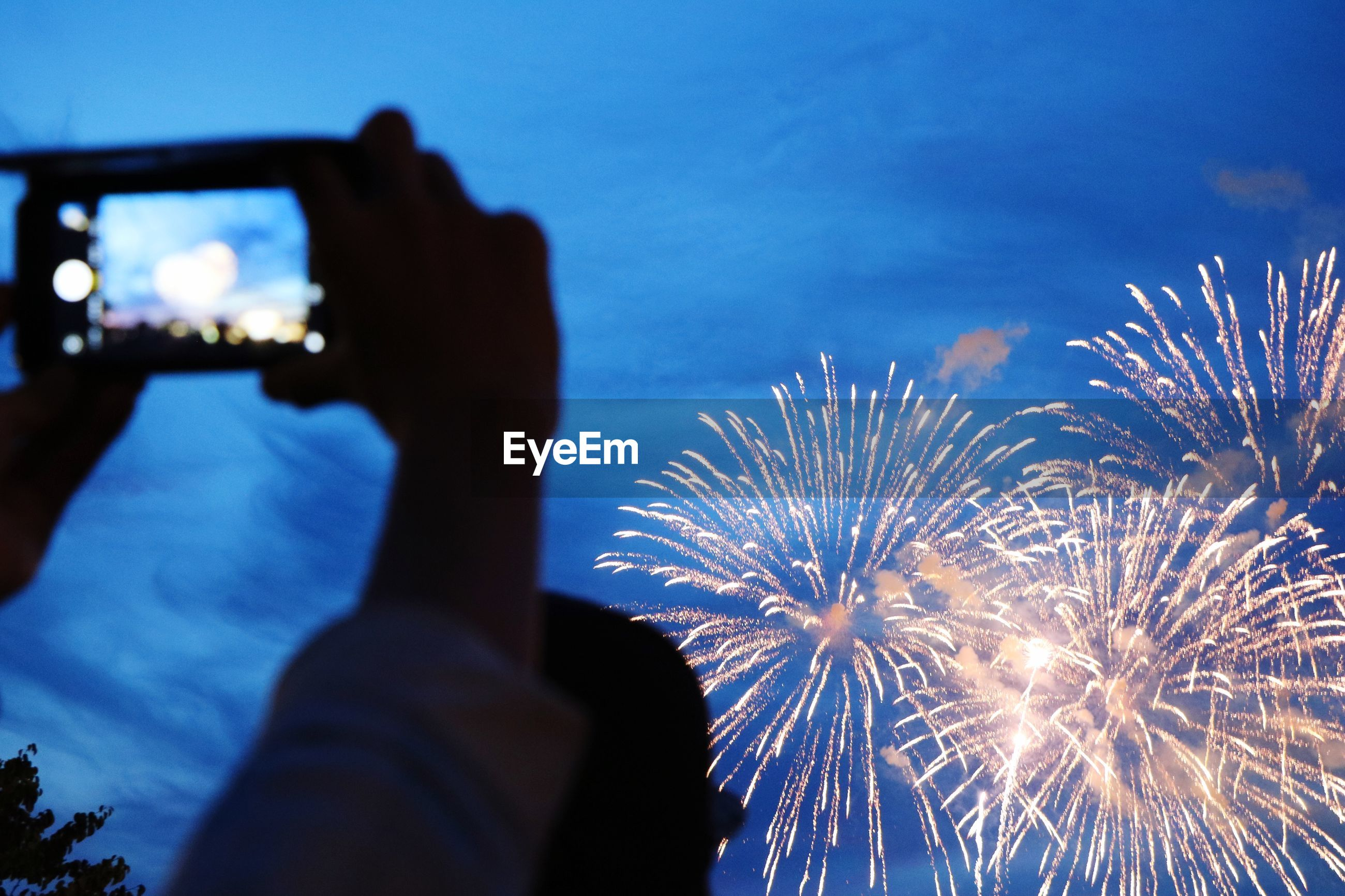 Close-up of person photographing firework at night