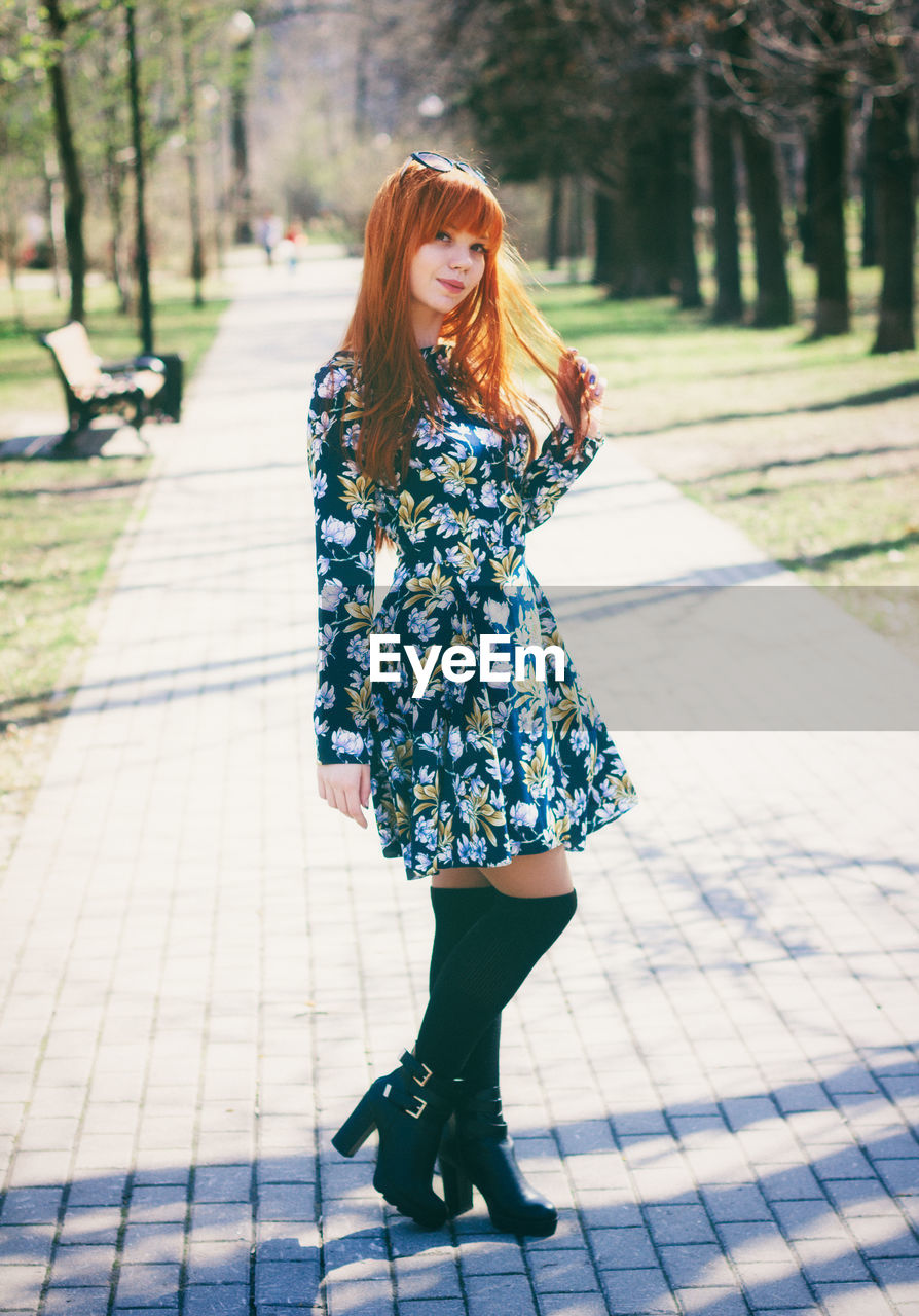 Full Length Of Young Woman Standing In Park