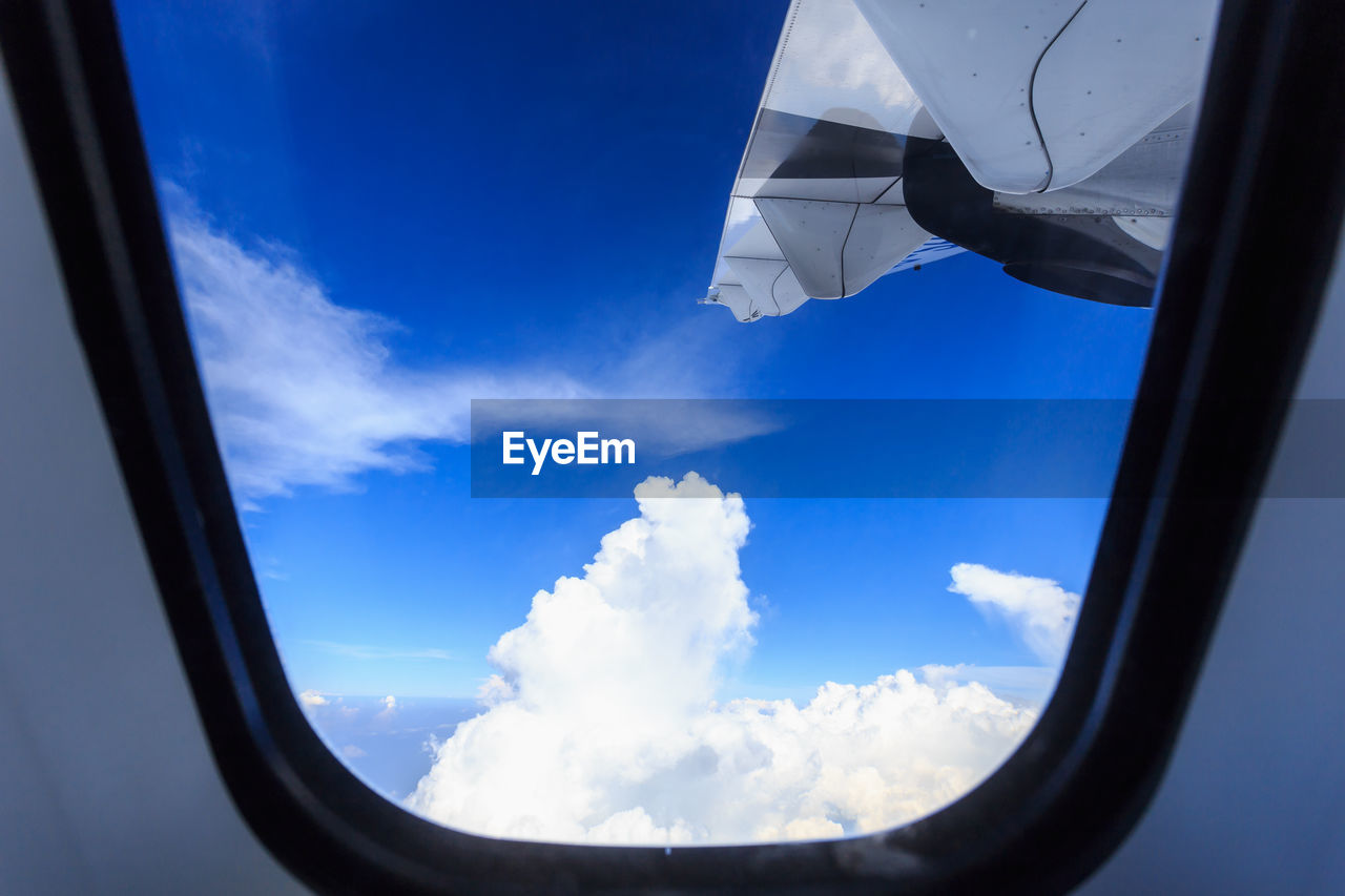 cloud - sky, sky, transparent, window, blue, day, mode of transportation, nature, vehicle interior, glass - material, air vehicle, beauty in nature, outdoors, transportation, airplane, no people, reflection, scenics - nature, motion, sunlight