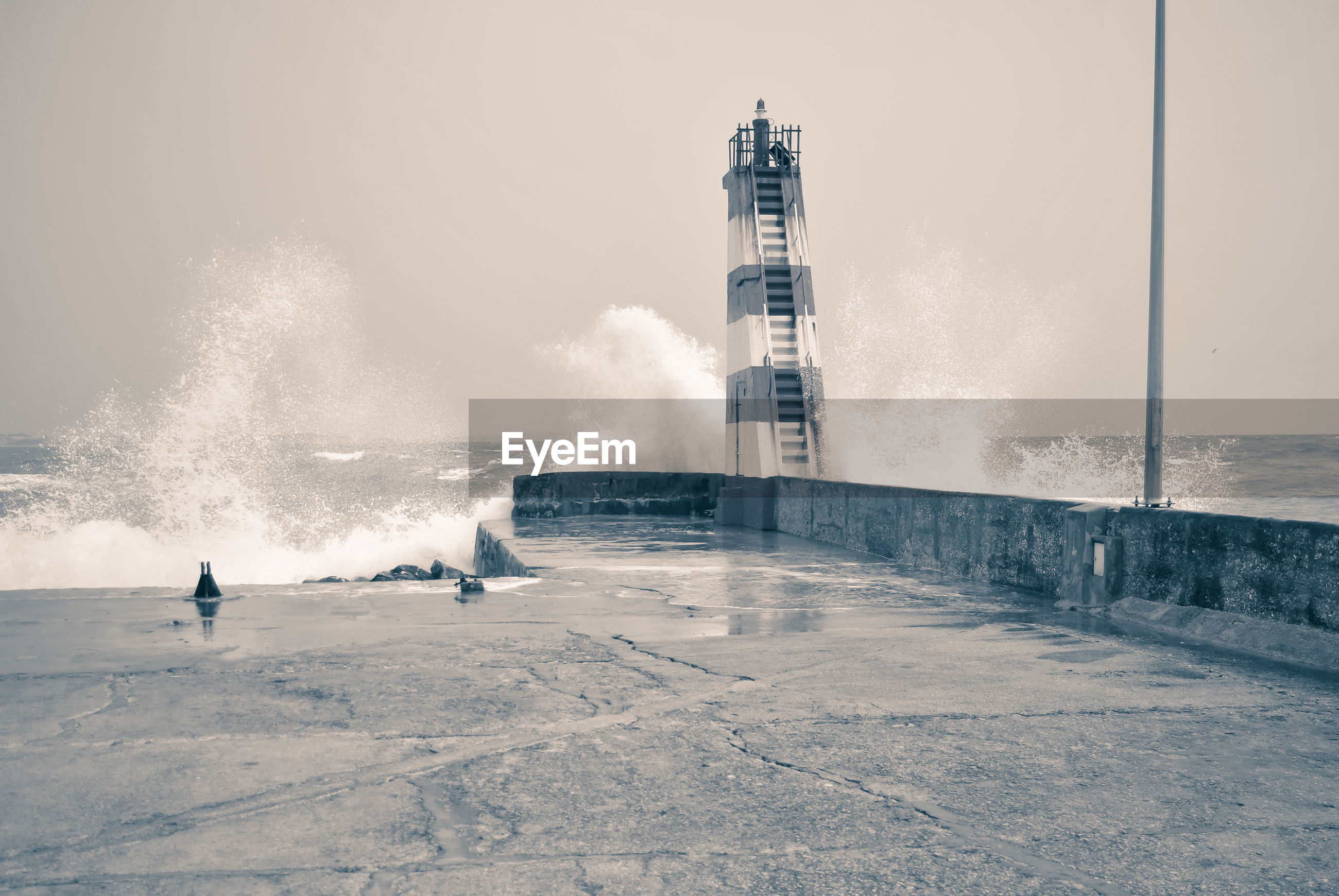 MAN STANDING BY LIGHTHOUSE AGAINST SEA