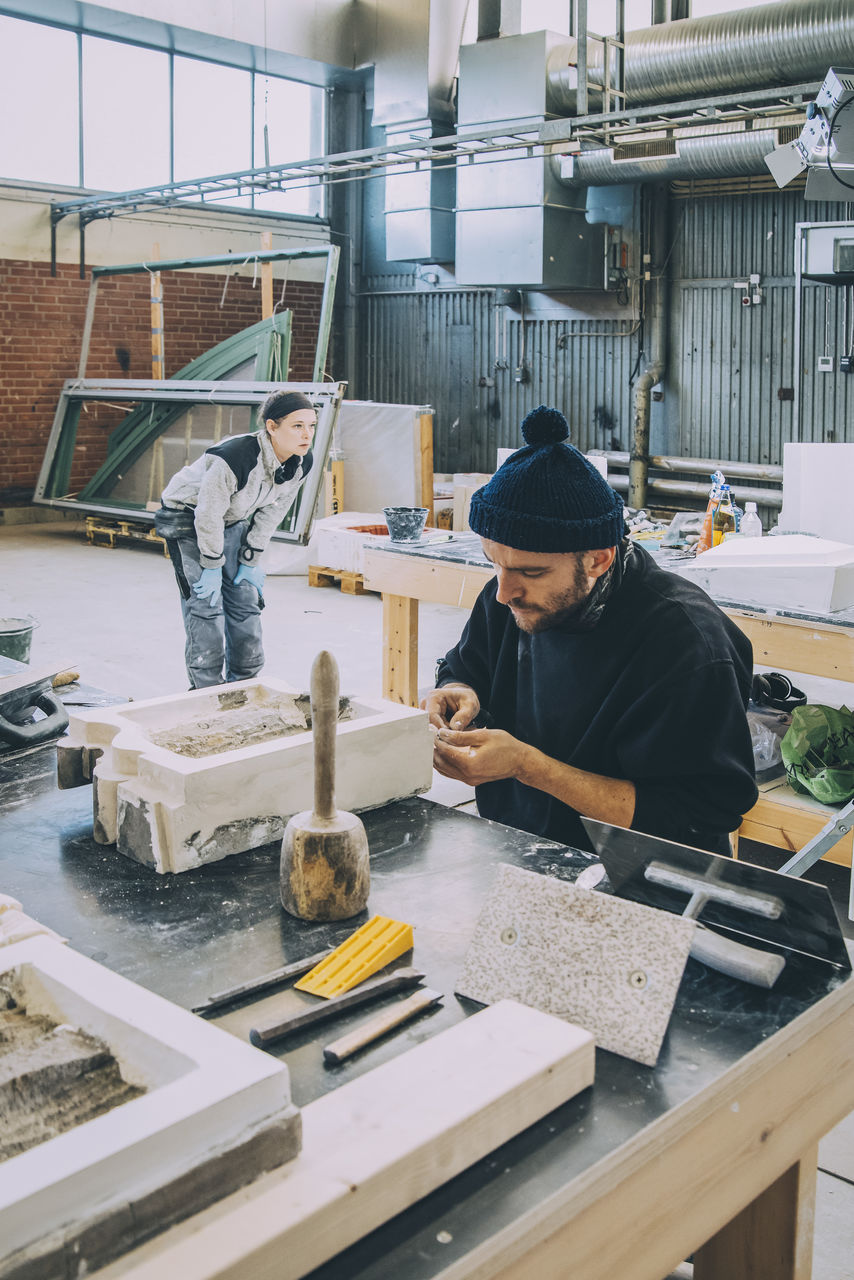 real people, occupation, working, one person, men, holding, art and craft, concentration, craft, workshop, three quarter length, standing, creativity, skill, indoors, day, young men, wood - material, casual clothing, preparation, workbench