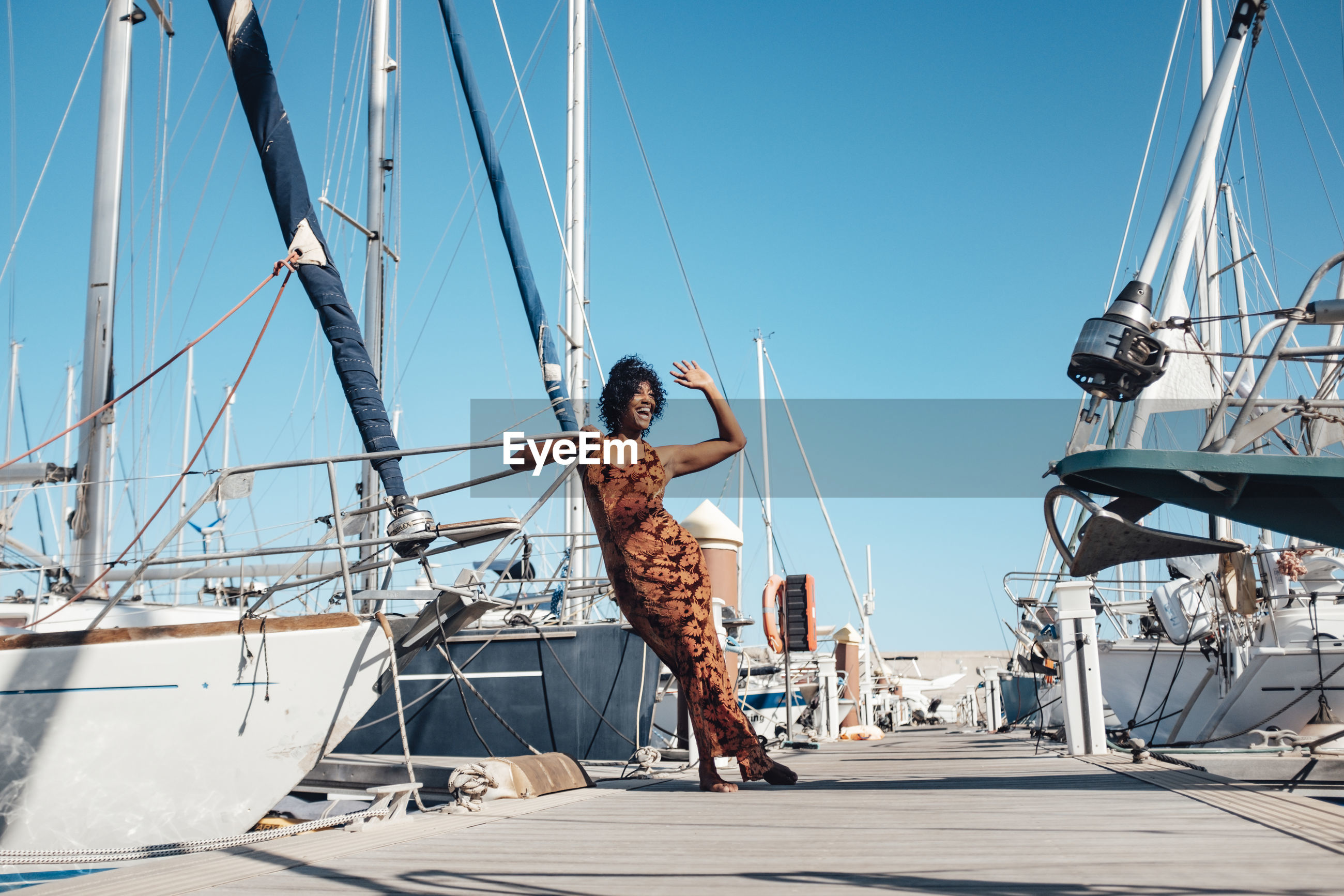 WOMAN ON SAILBOAT AGAINST SKY