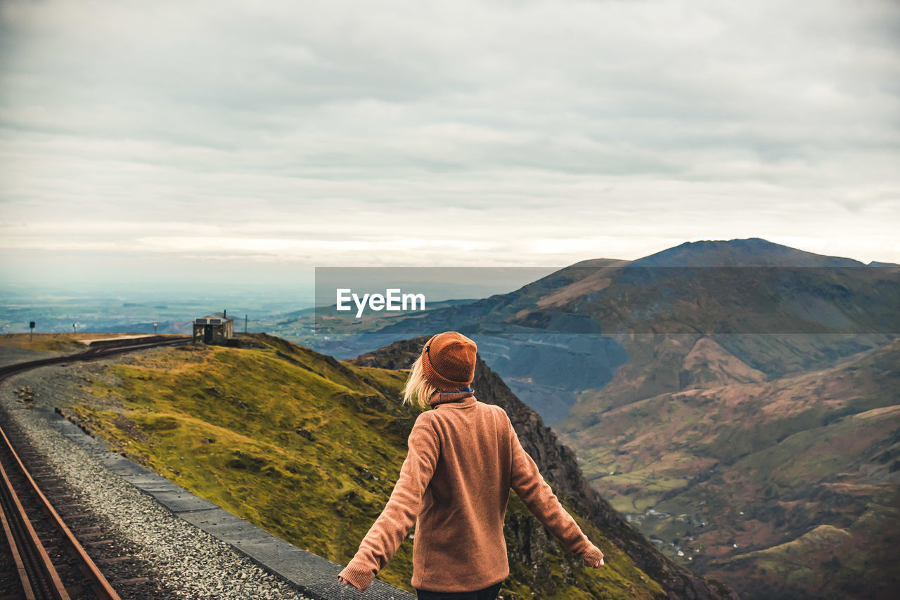 Rear View Of Woman Looking At Mountain Against Cloudy Sky