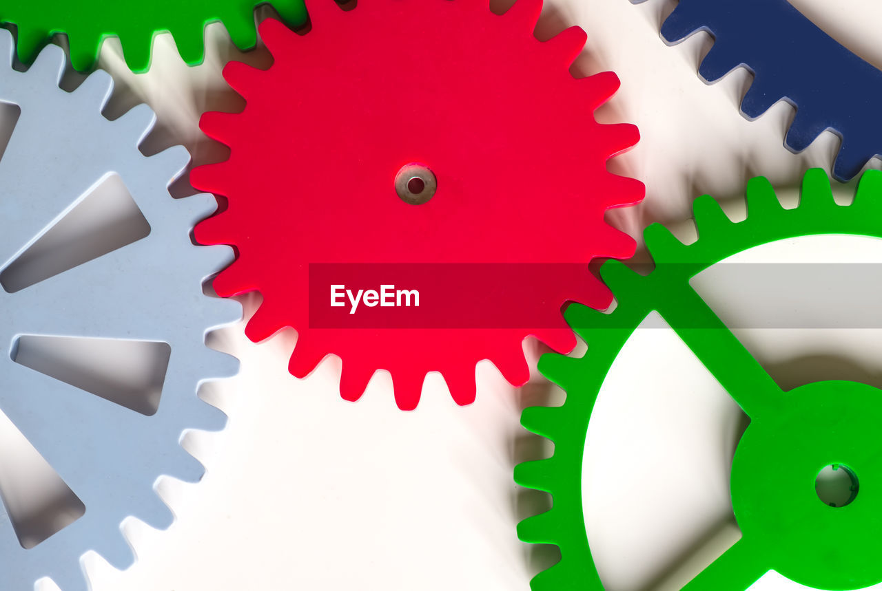 Close-up of colorful gears against white background