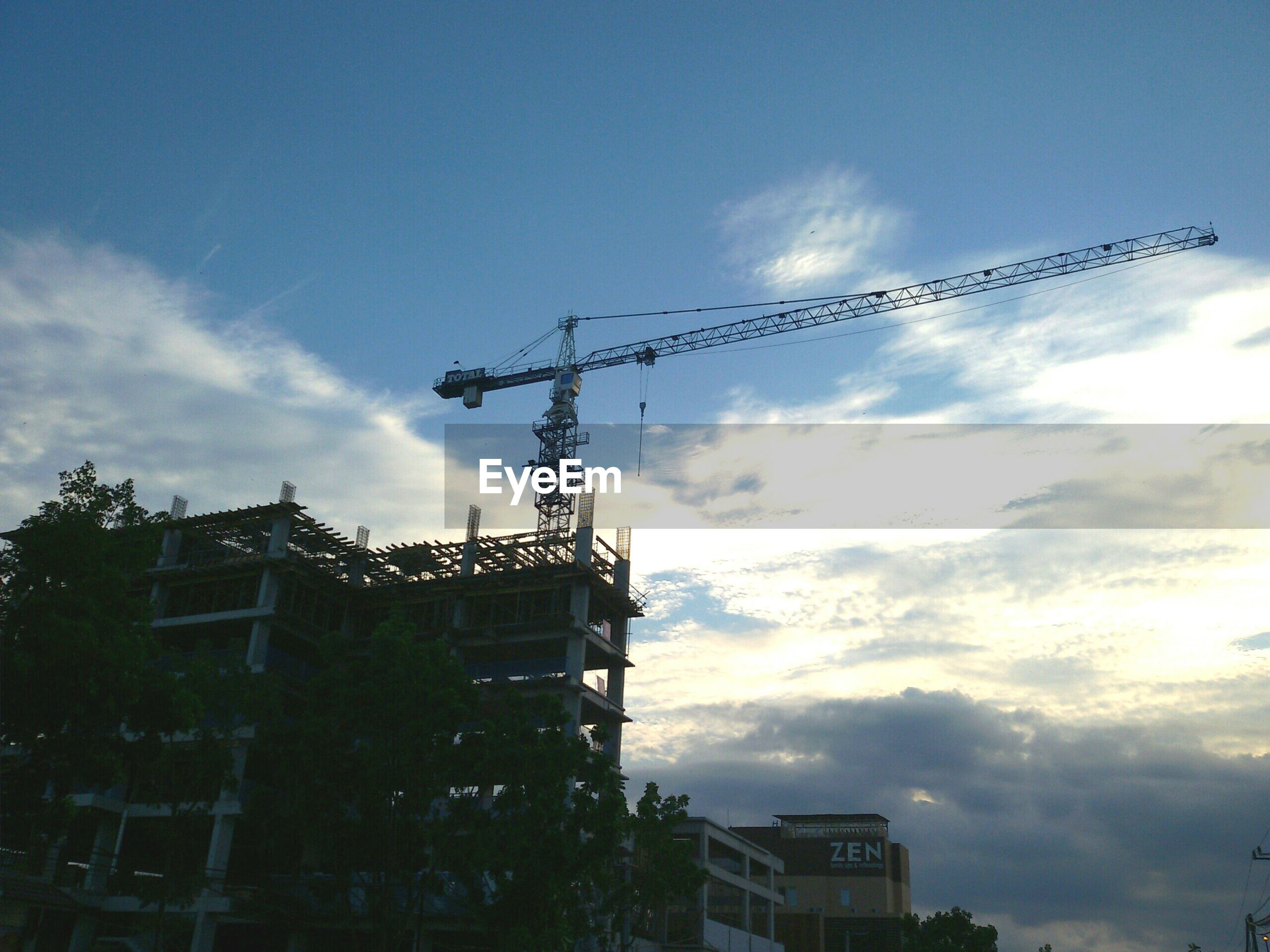 building exterior, architecture, built structure, low angle view, sky, crane - construction machinery, cloud - sky, construction site, development, building, city, crane, outdoors, cloud, flying, residential building, no people, residential structure, day, cloudy