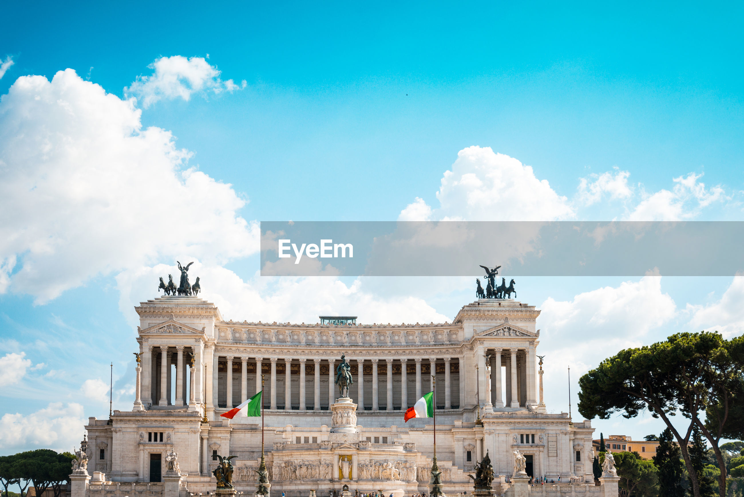 Italian flags by altare della patria against cloudy sky