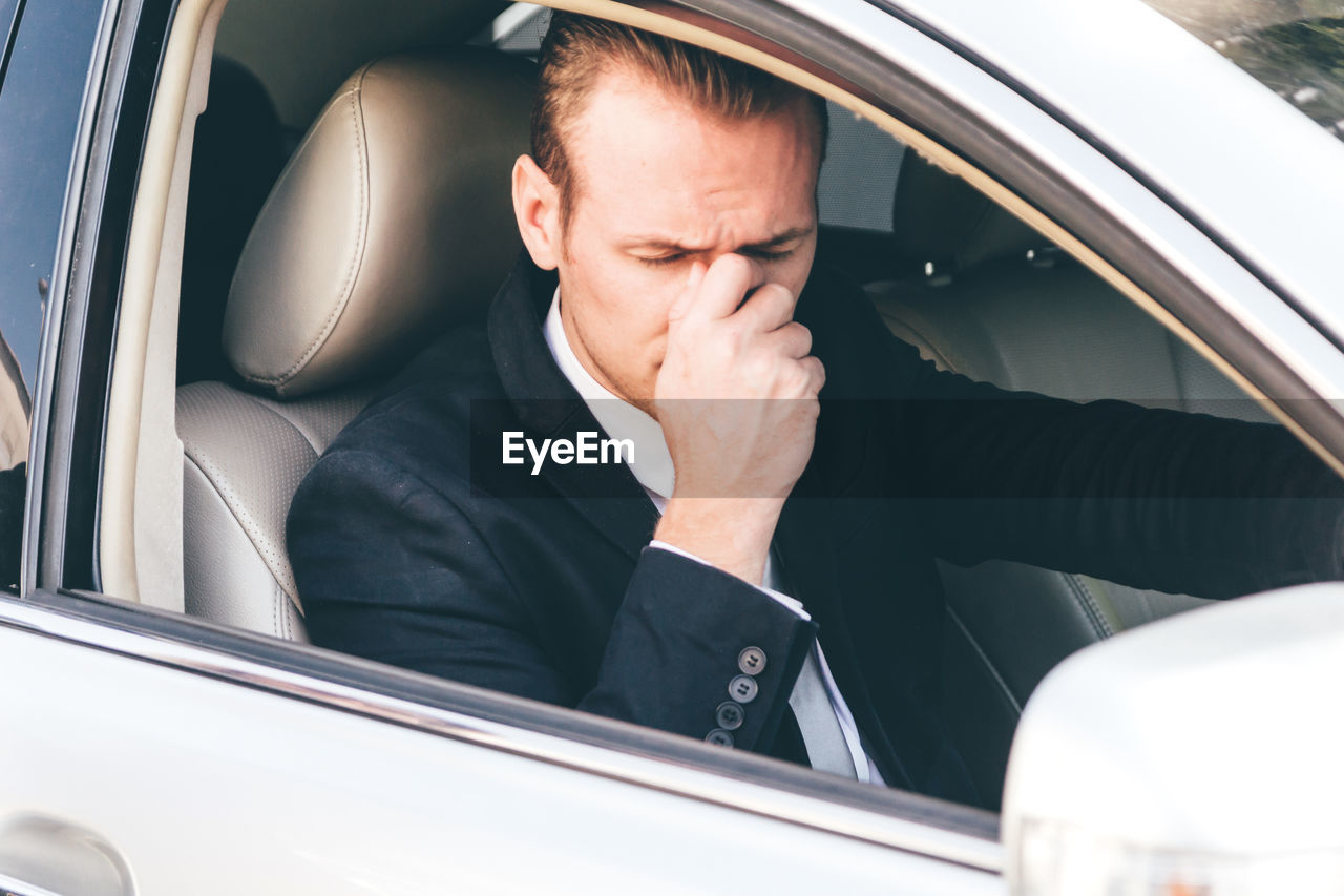 Worried businessman sitting in car