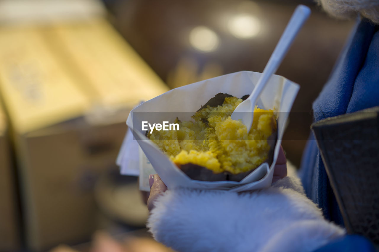 food and drink, one person, food, holding, freshness, hand, real people, human hand, human body part, selective focus, indoors, close-up, midsection, ready-to-eat, kitchen utensil, eating utensil, lifestyles, unrecognizable person, eating, take out food, snack