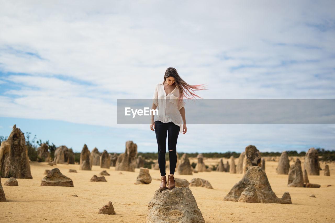 Woman standing on rock in landscape against sky