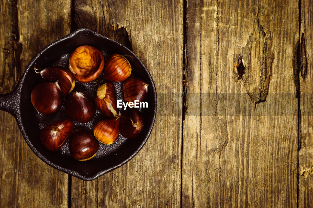 wood - material, food and drink, food, directly above, bowl, healthy eating, table, wellbeing, high angle view, freshness, no people, indoors, fruit, still life, brown, kitchen utensil, close-up, chestnut, wood, textured, wood grain